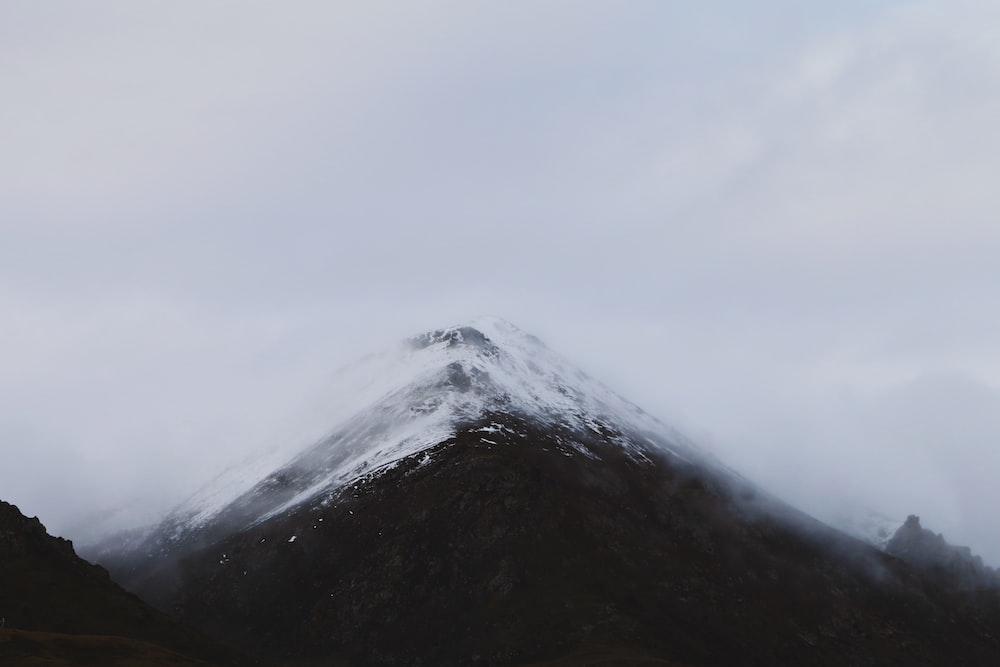 snow mountain summit under clouds