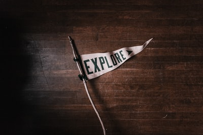 A white pennant that says explore on a dark wooden floor