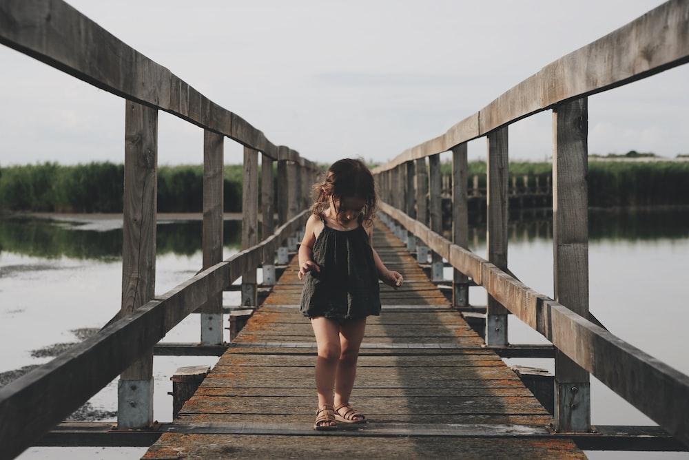 girl wearing black camisole walking on dock