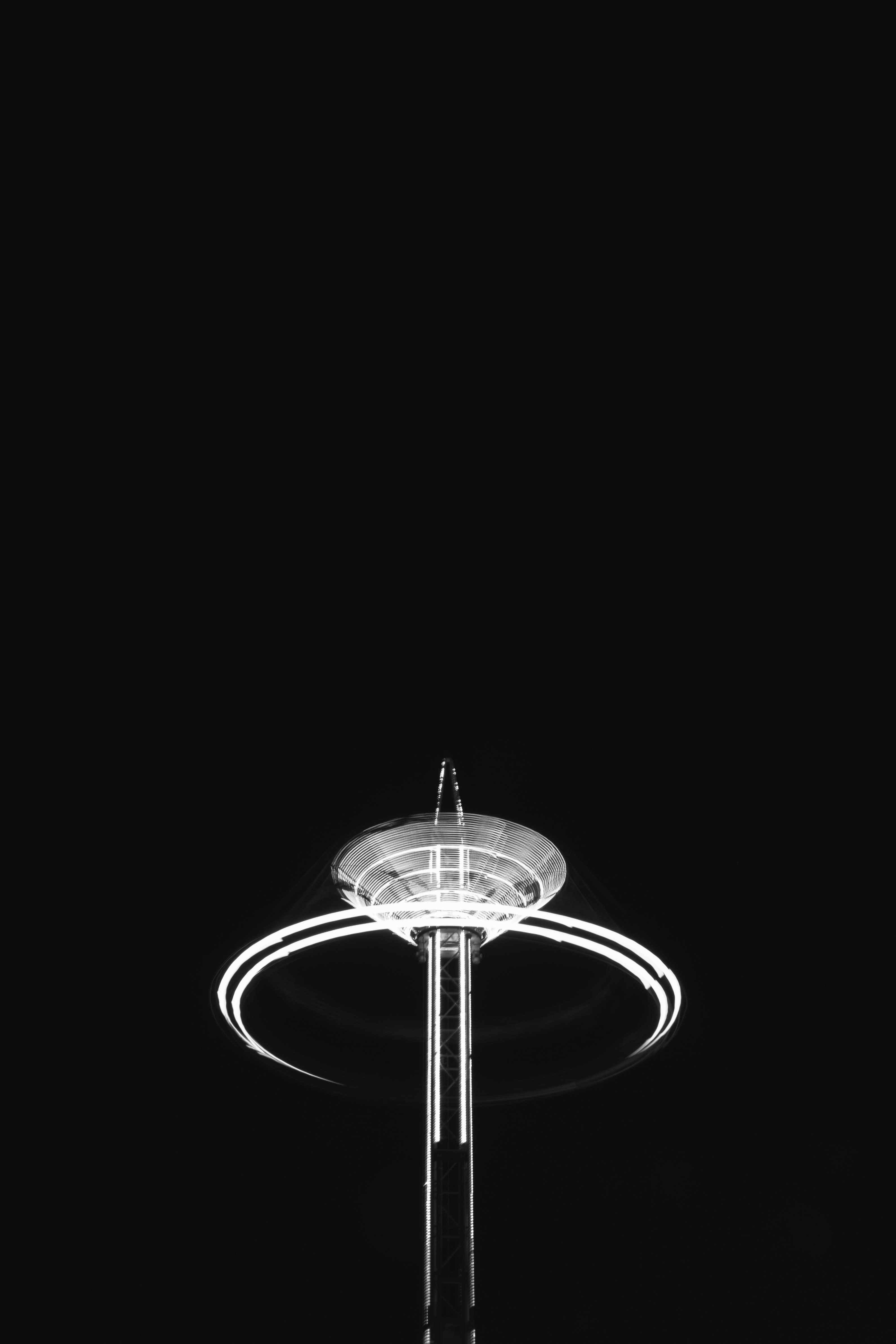 A black ground with an illuminated fairground ride, lit up with a surrounding light trail circle