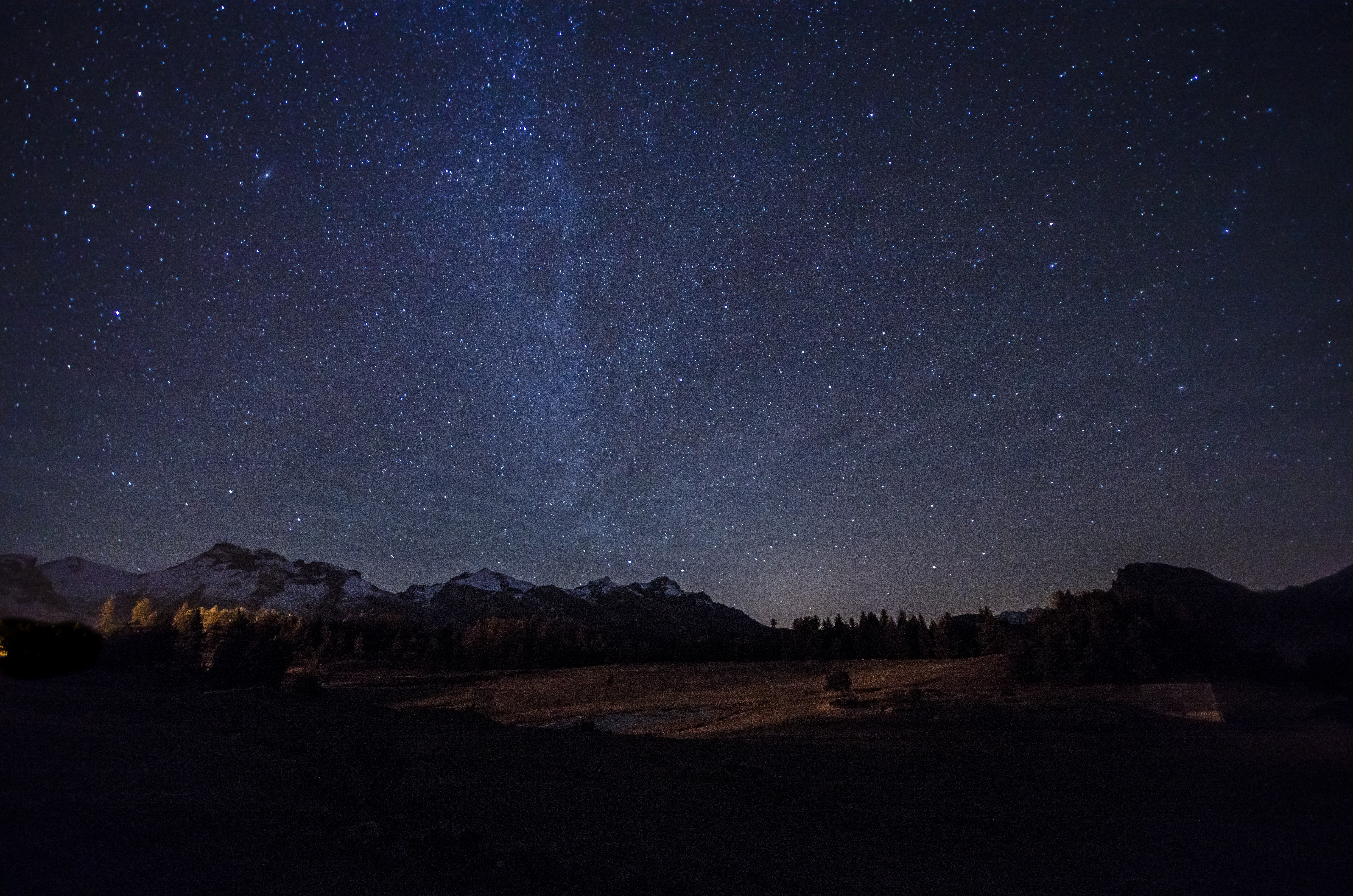 Starry sky over mountains and woods