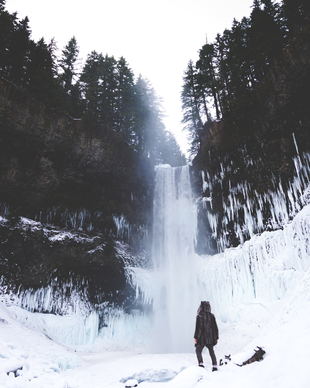 person standing looking at water falls covered by snows