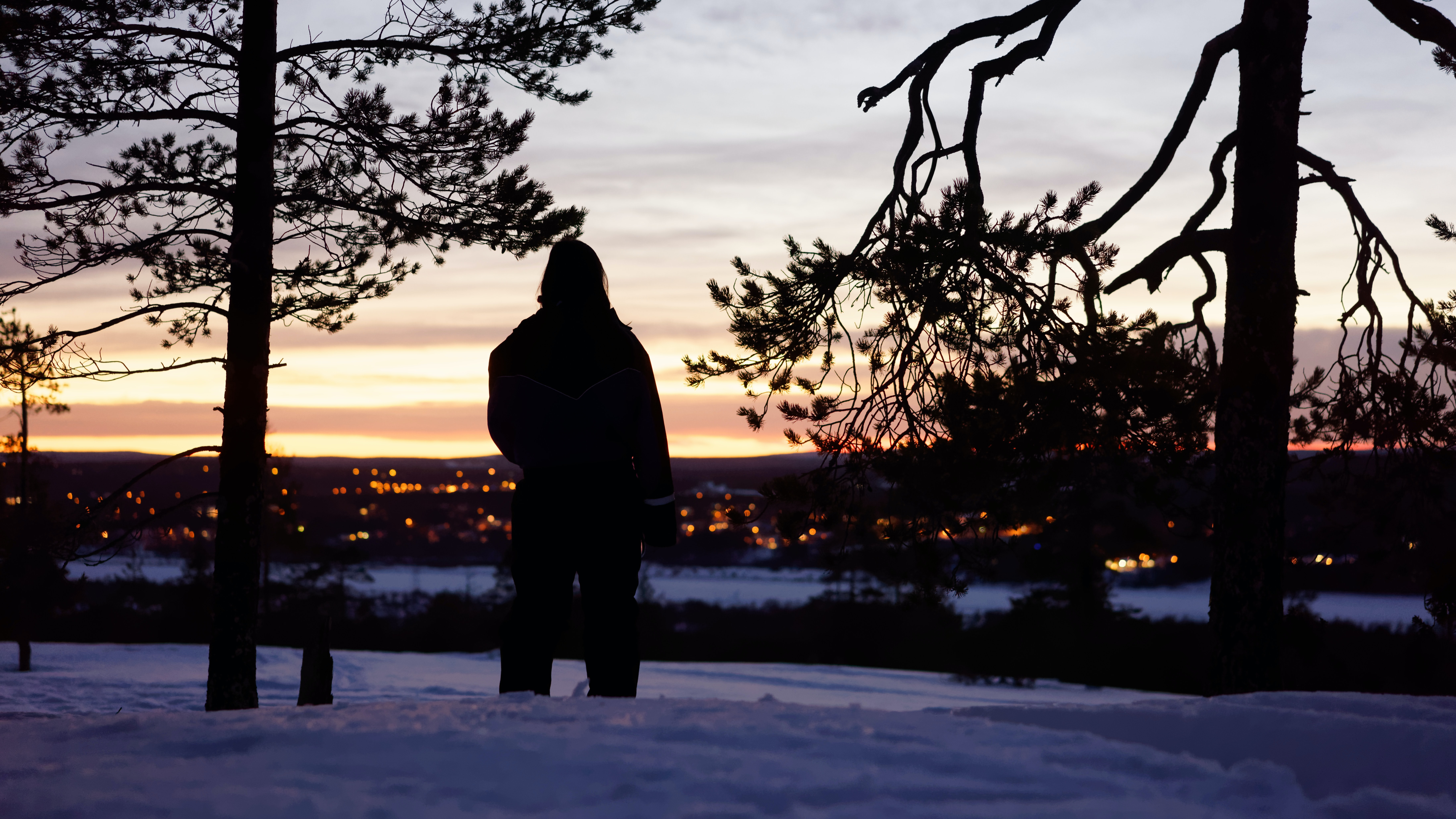 A person stands silhouetted on a snowy tree-lined road, looking at the lights shining from Riovenni
