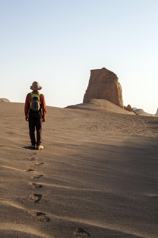 man wearing hat walking on desert