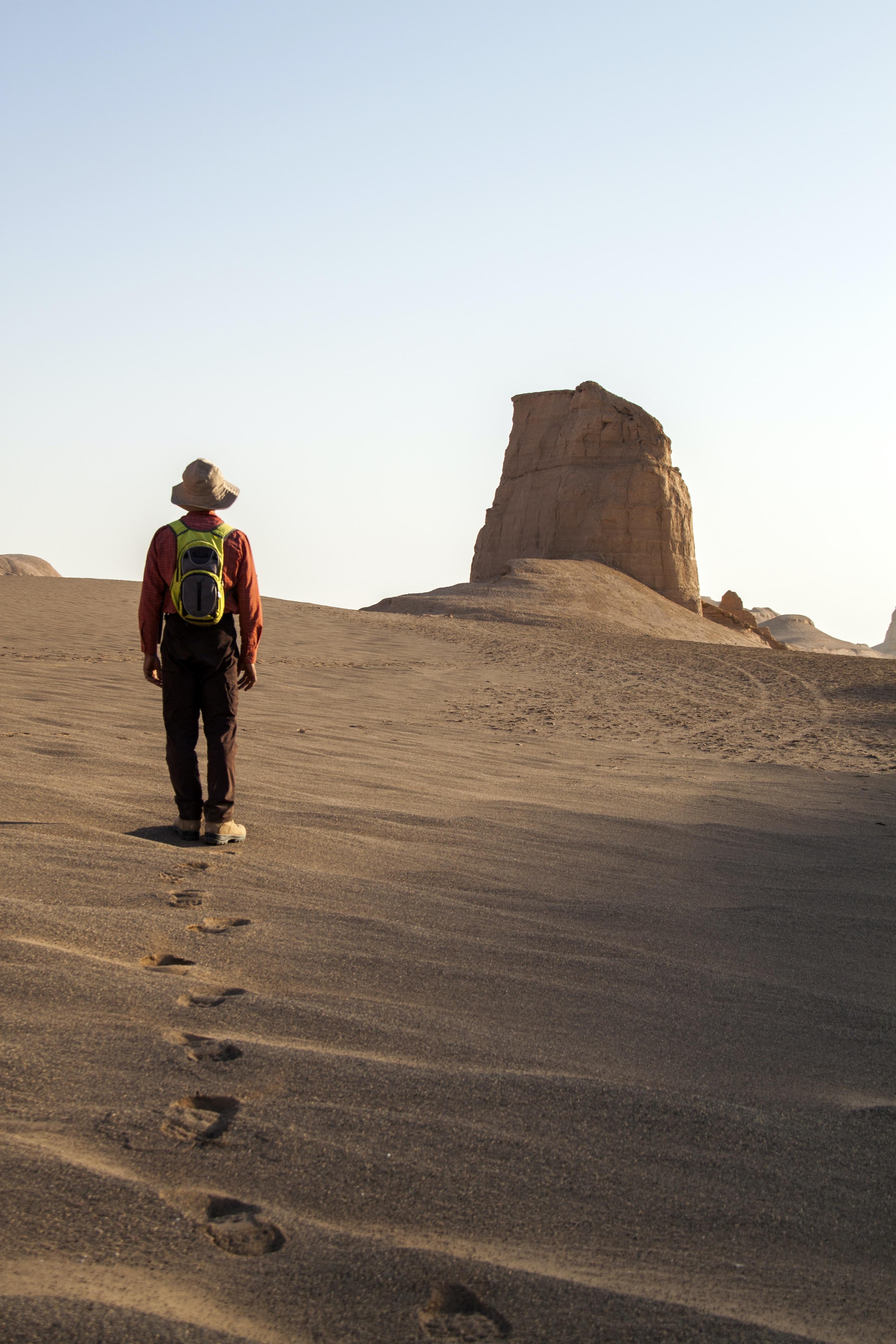 Hiker walks alone through the dry sands of shahdad desert