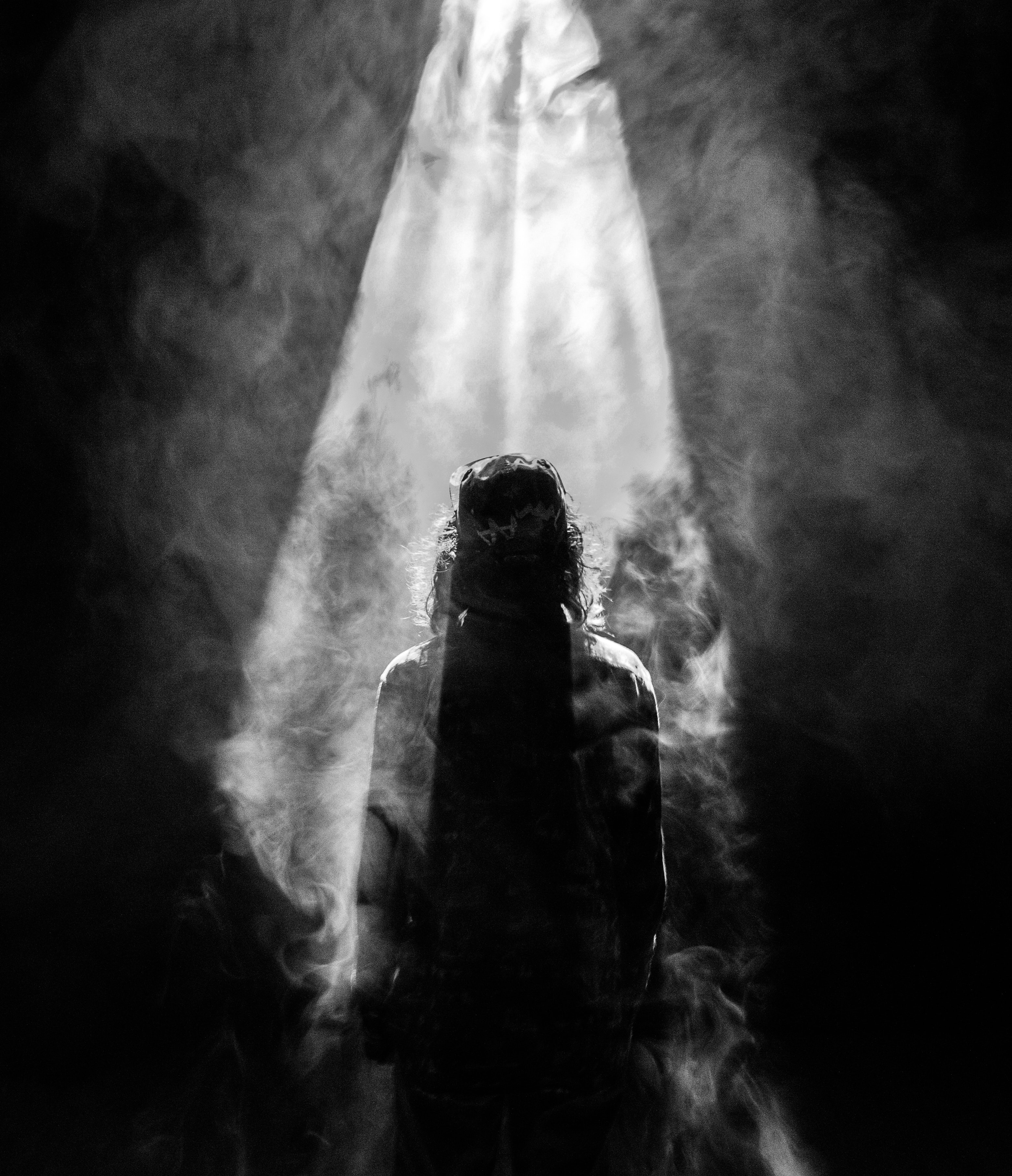 A black-and-white shot of a person's silhouette engulfed in smoke
