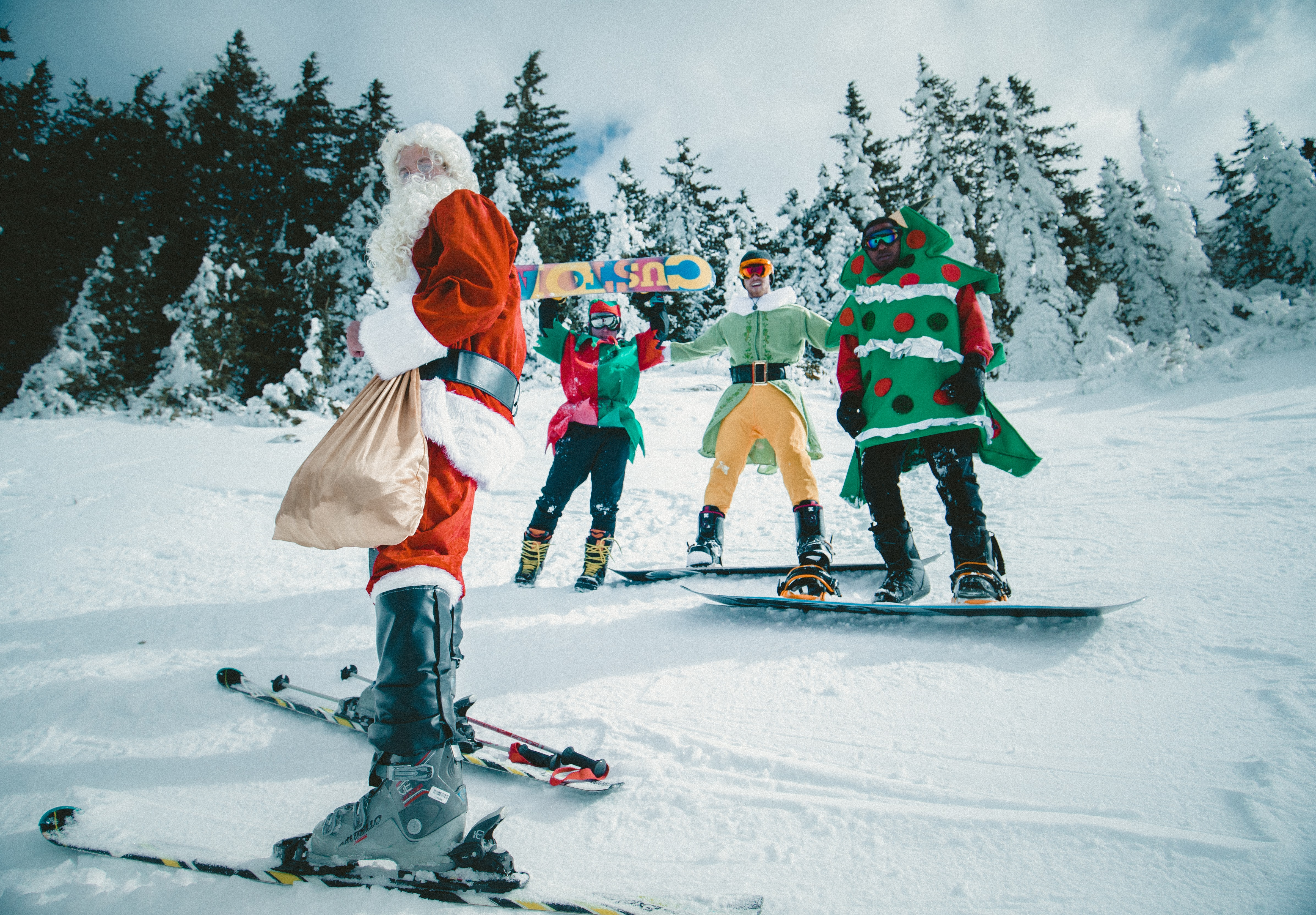 A man dressed as Father Christmas holding a sack and skiing on snow in front of trees, with people on snowboards dressed as elves and a Christmas tree behind him