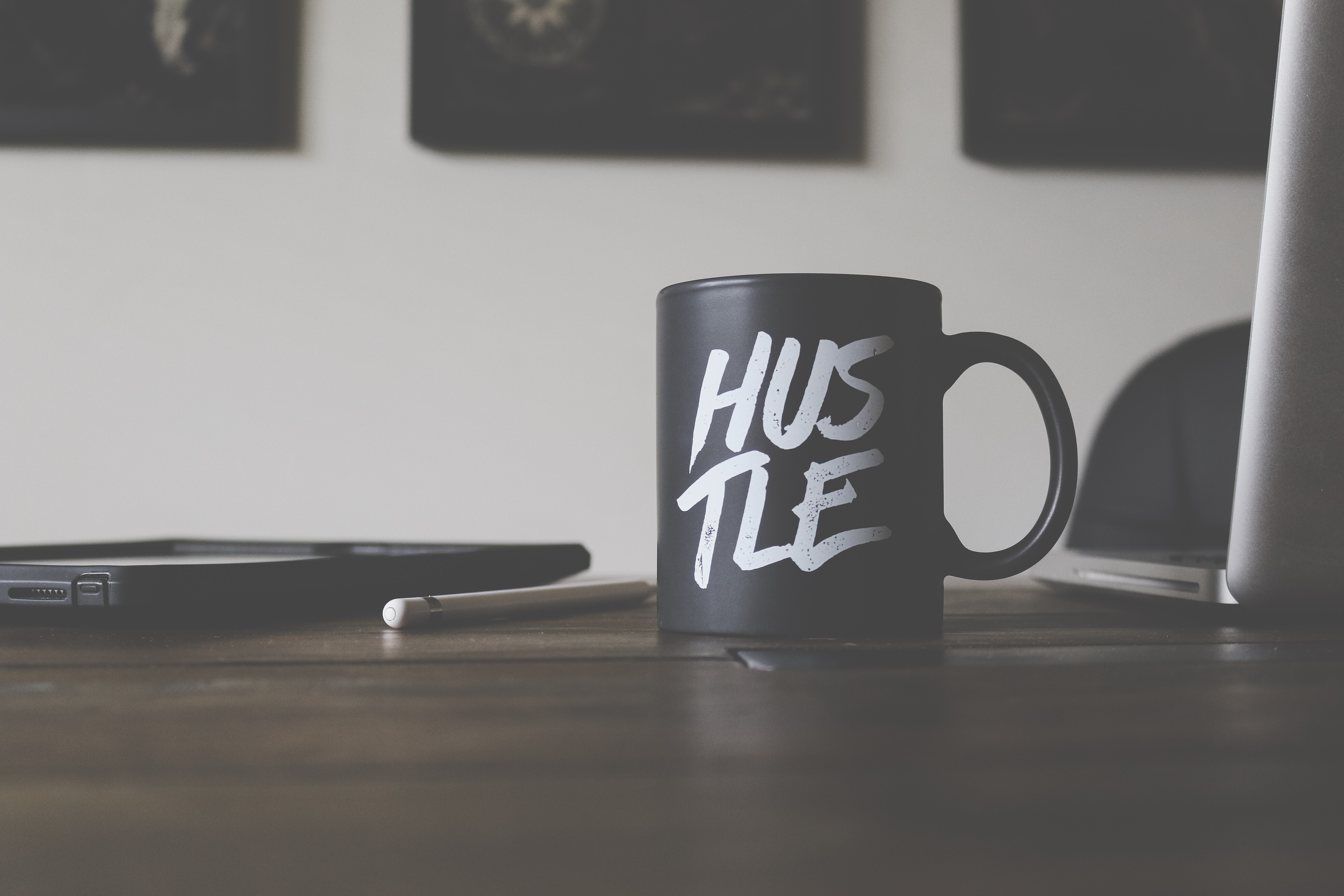 "A black mug sitting on an office desk in Missoula with white writing which says ""Hustle"""
