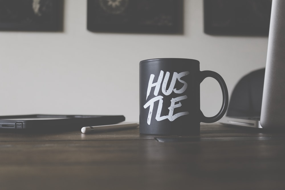black and white Hustle-printed ceramic mug on table