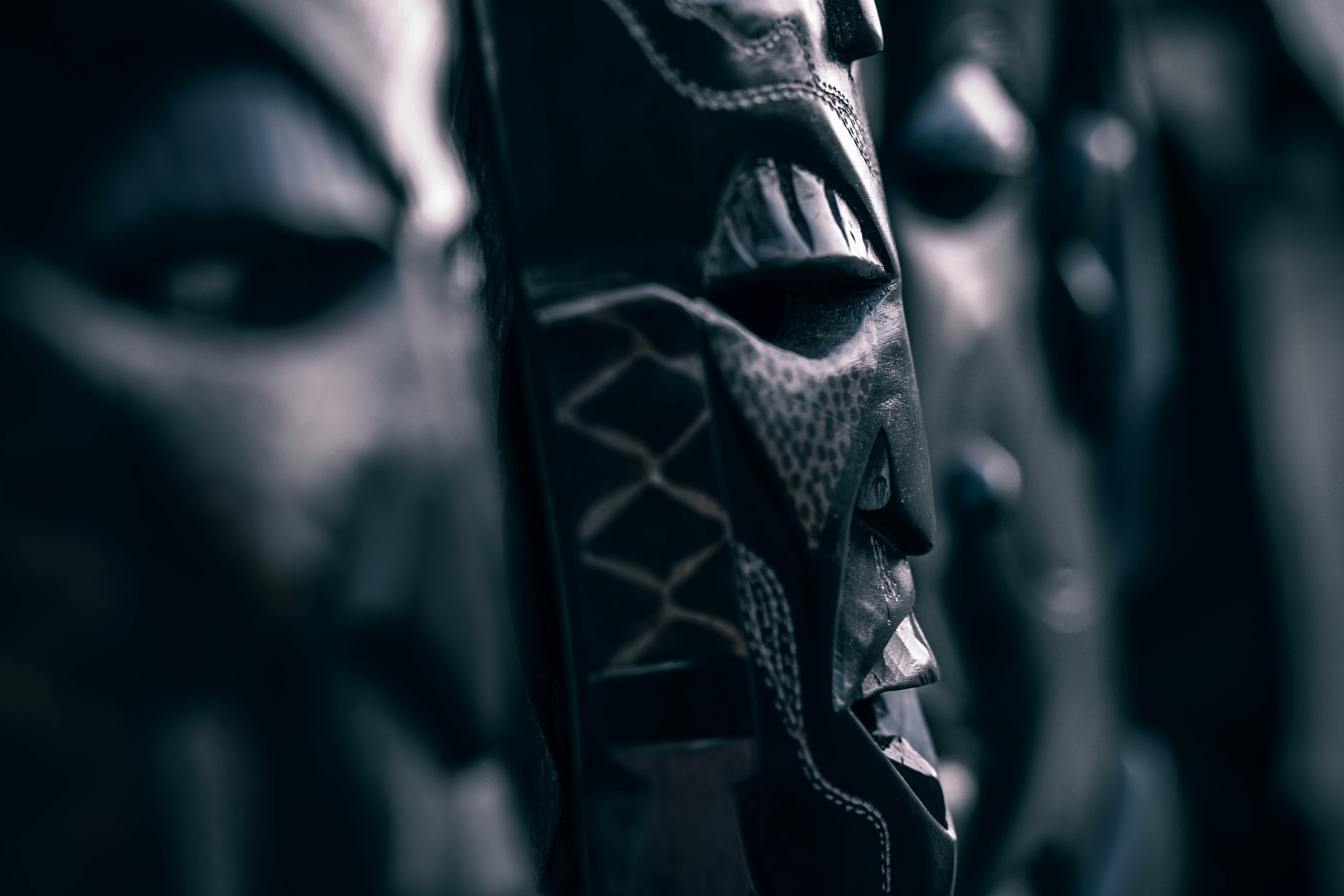 A dim close-up of wooden  tribal masks