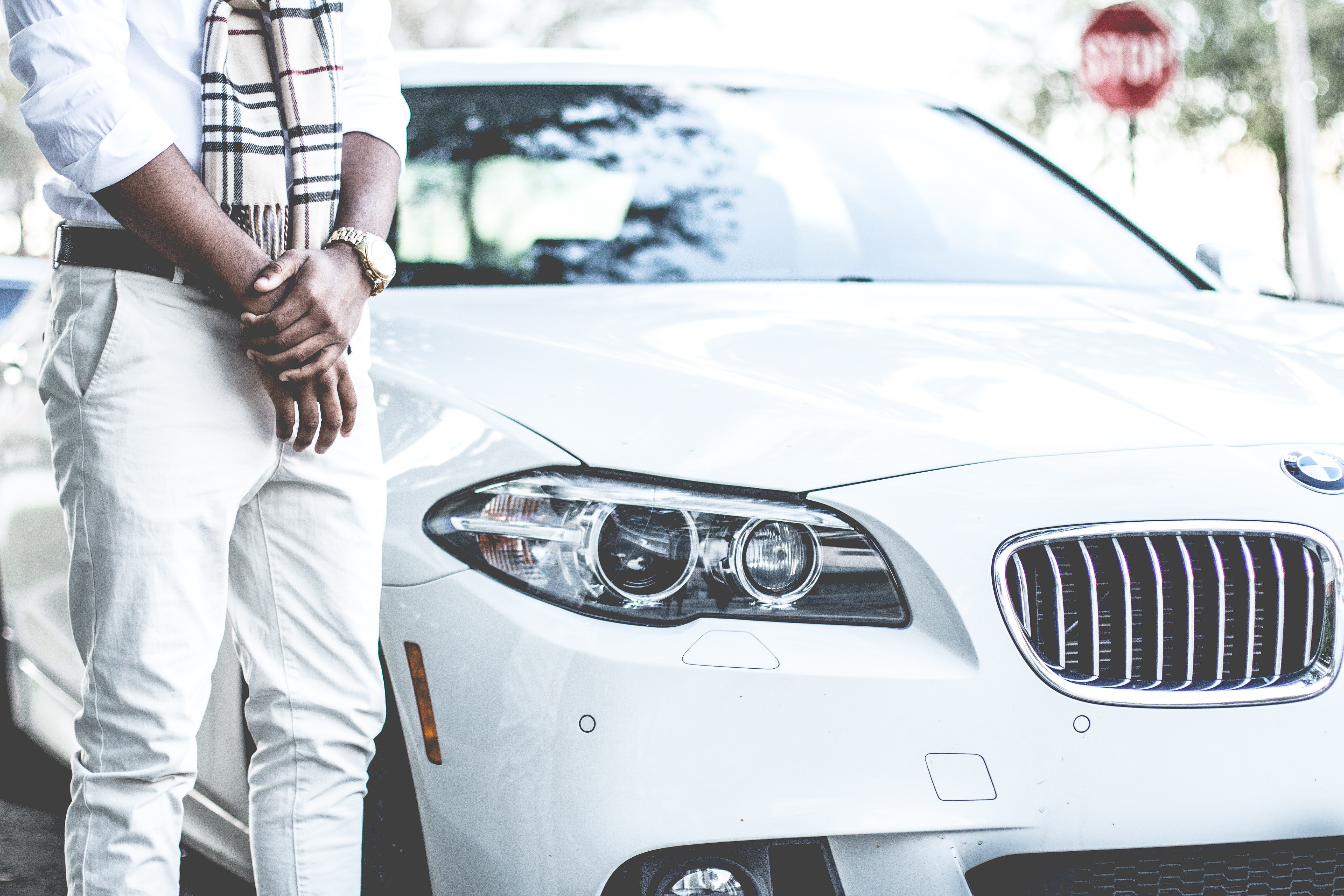 person standing beside the white BMW car