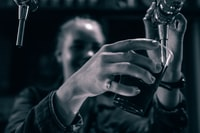 grayscale photo of person holding drinking glass