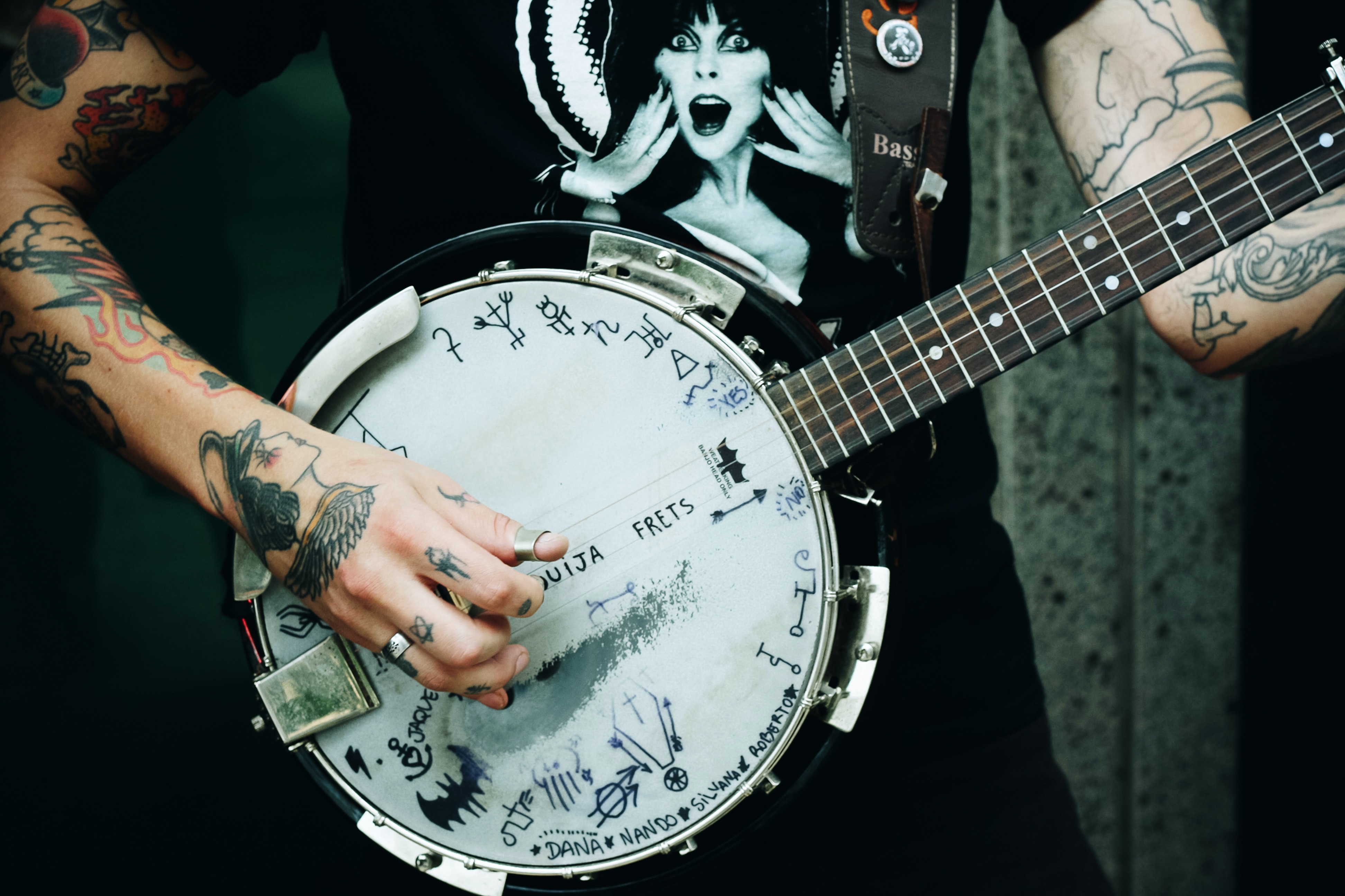 A musician playing the banjo with playful doodles on its white head