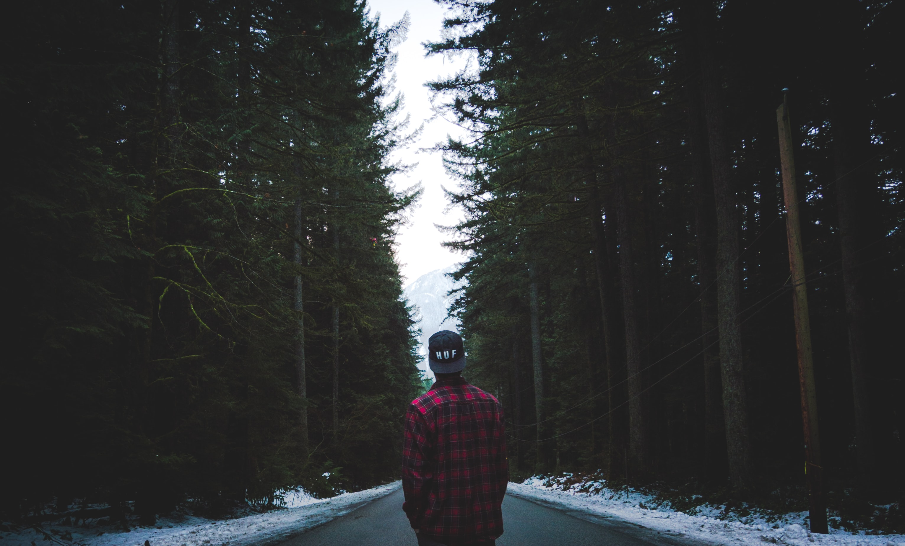 A man in a red plaid shirt with a backwards hat staring down a forest road during winter in Squamish, British Columbia