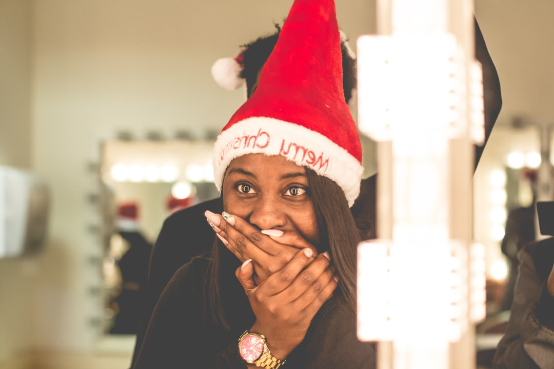 Woman with a merry Christmas cap smiling and watching herself in the mirror