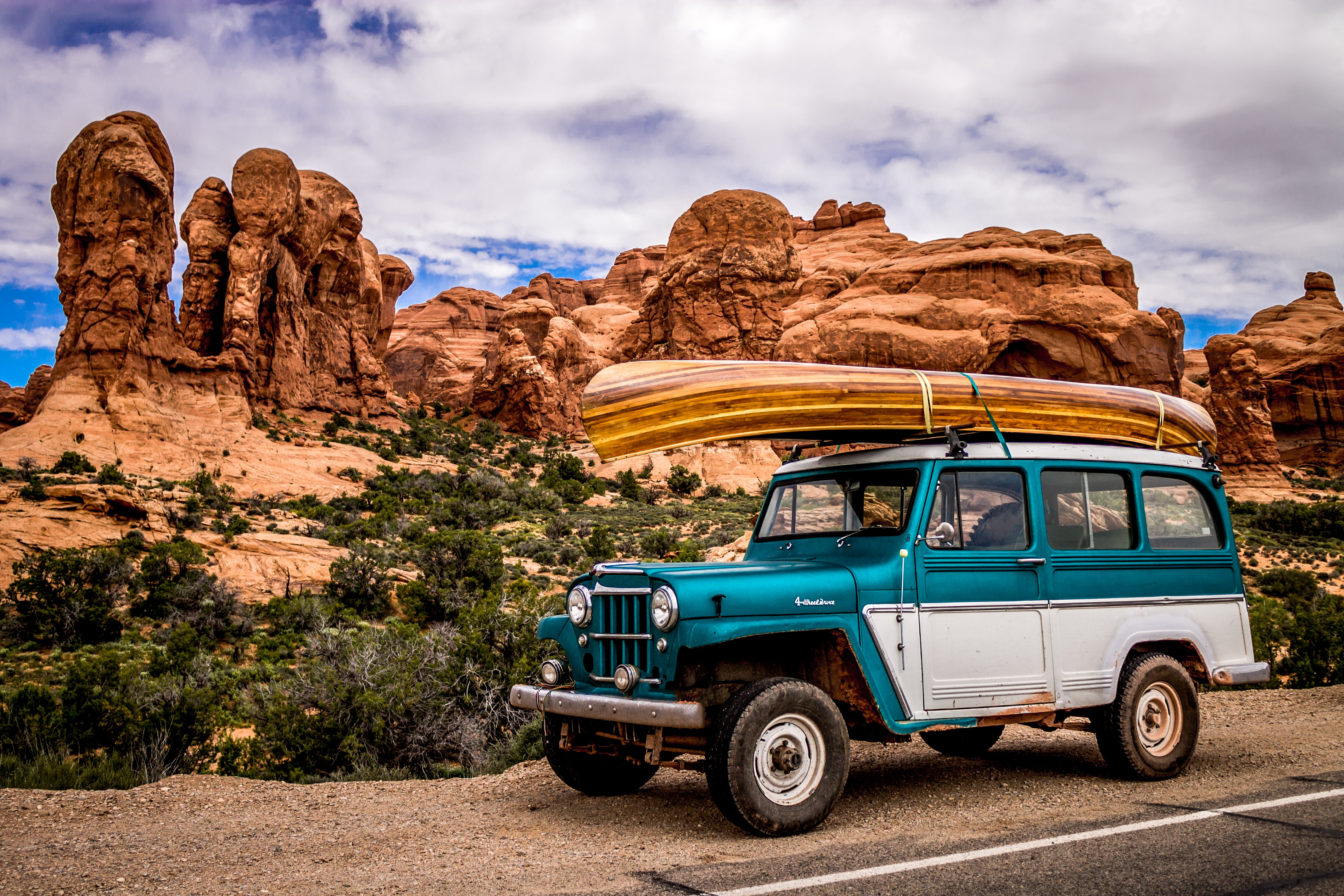 Retro jeep with wooden canoe on roof at side of road in Arches National Park
