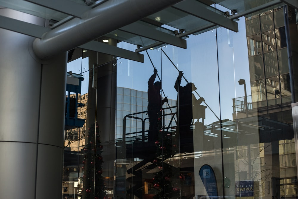 utility man standing in scissor platform cleaning glass window