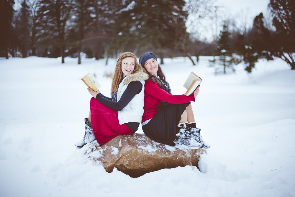two women sitting on rock while holding books