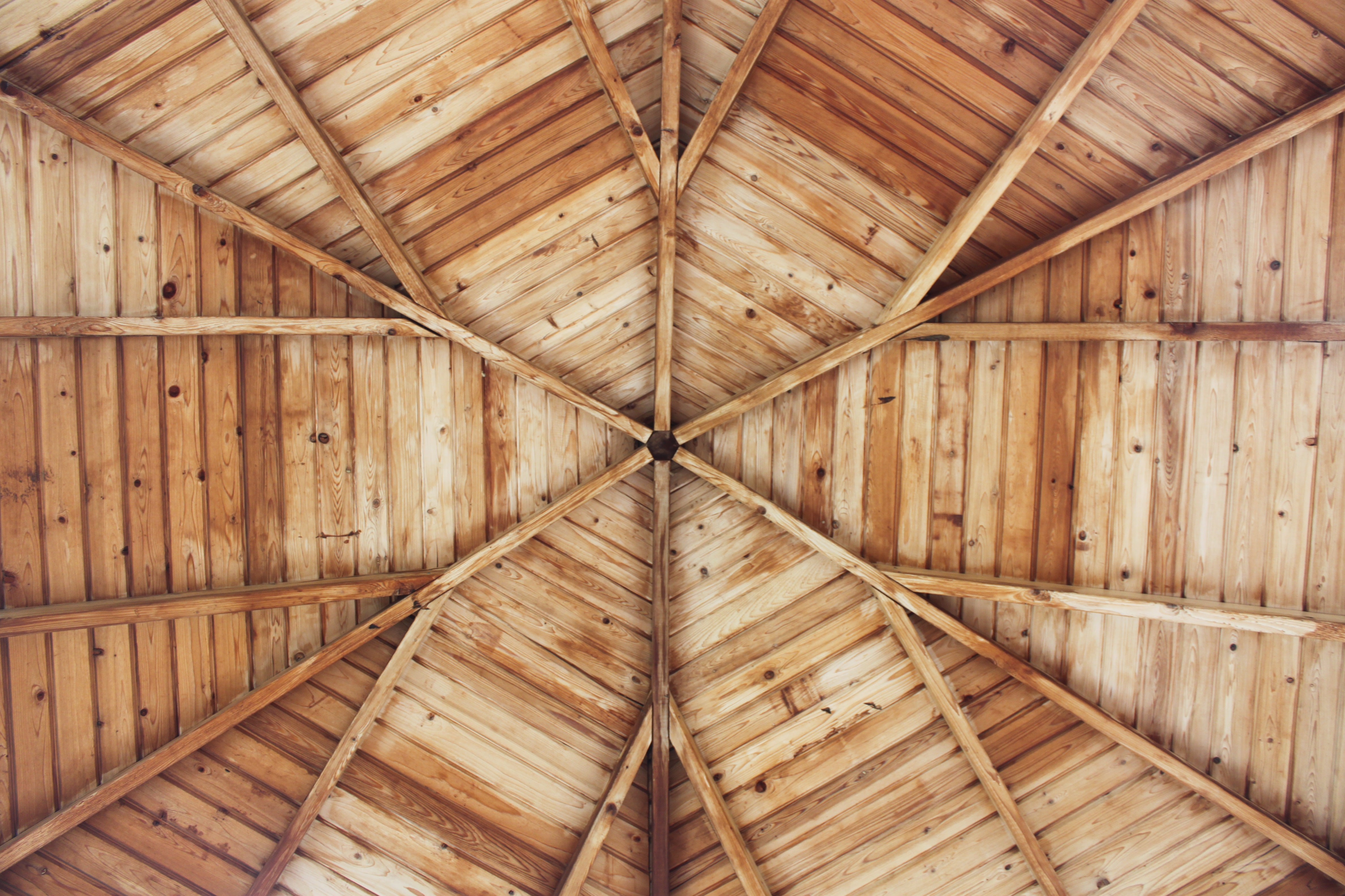 The symmetrical details of a wooden structure's ceiling.
