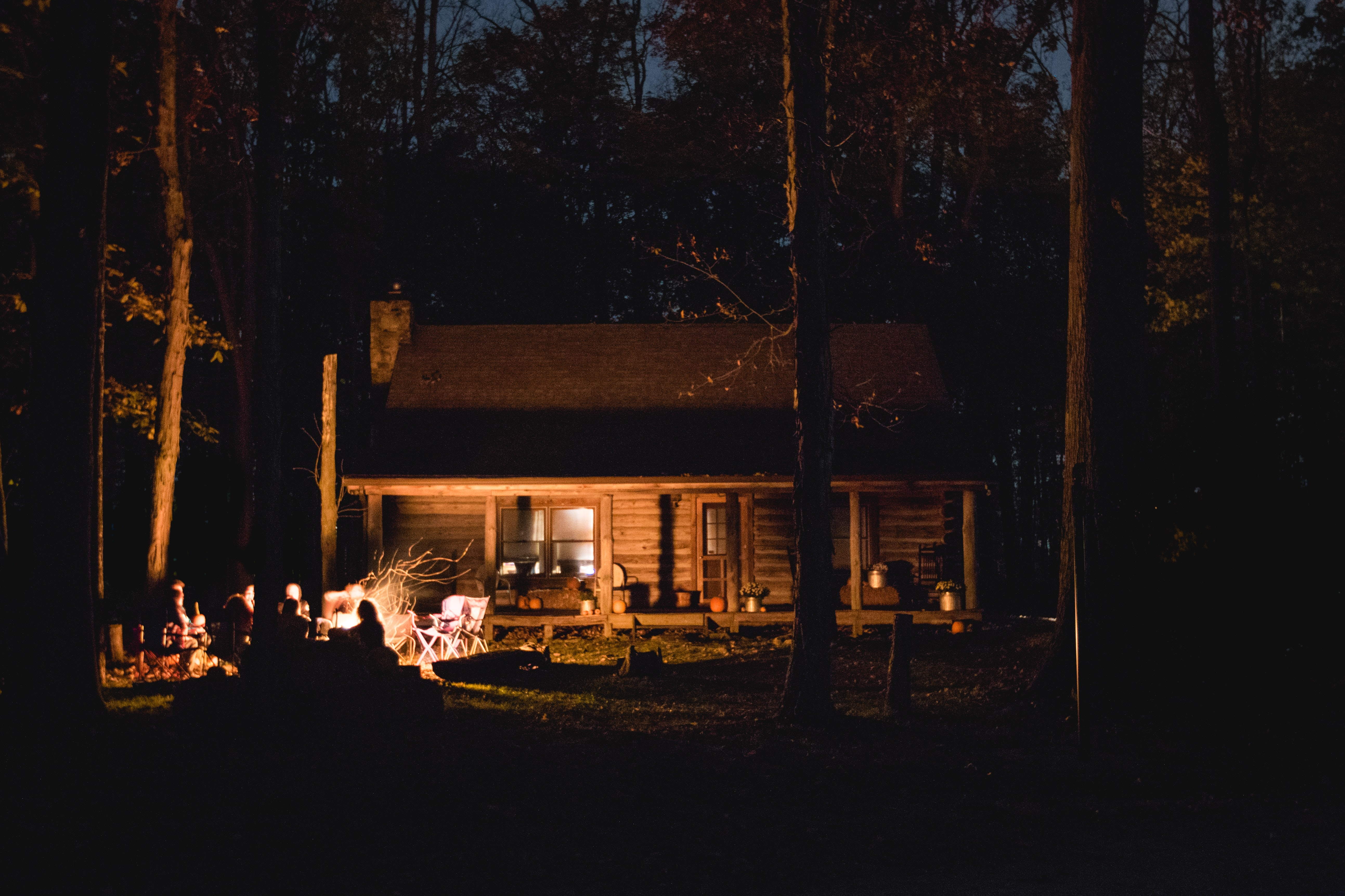 A group of people around a fire at night outside a woodland cabin