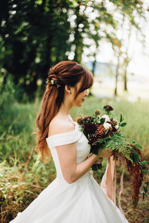 woman wearing white off-shoulder wedding gown wearing white petaled flower