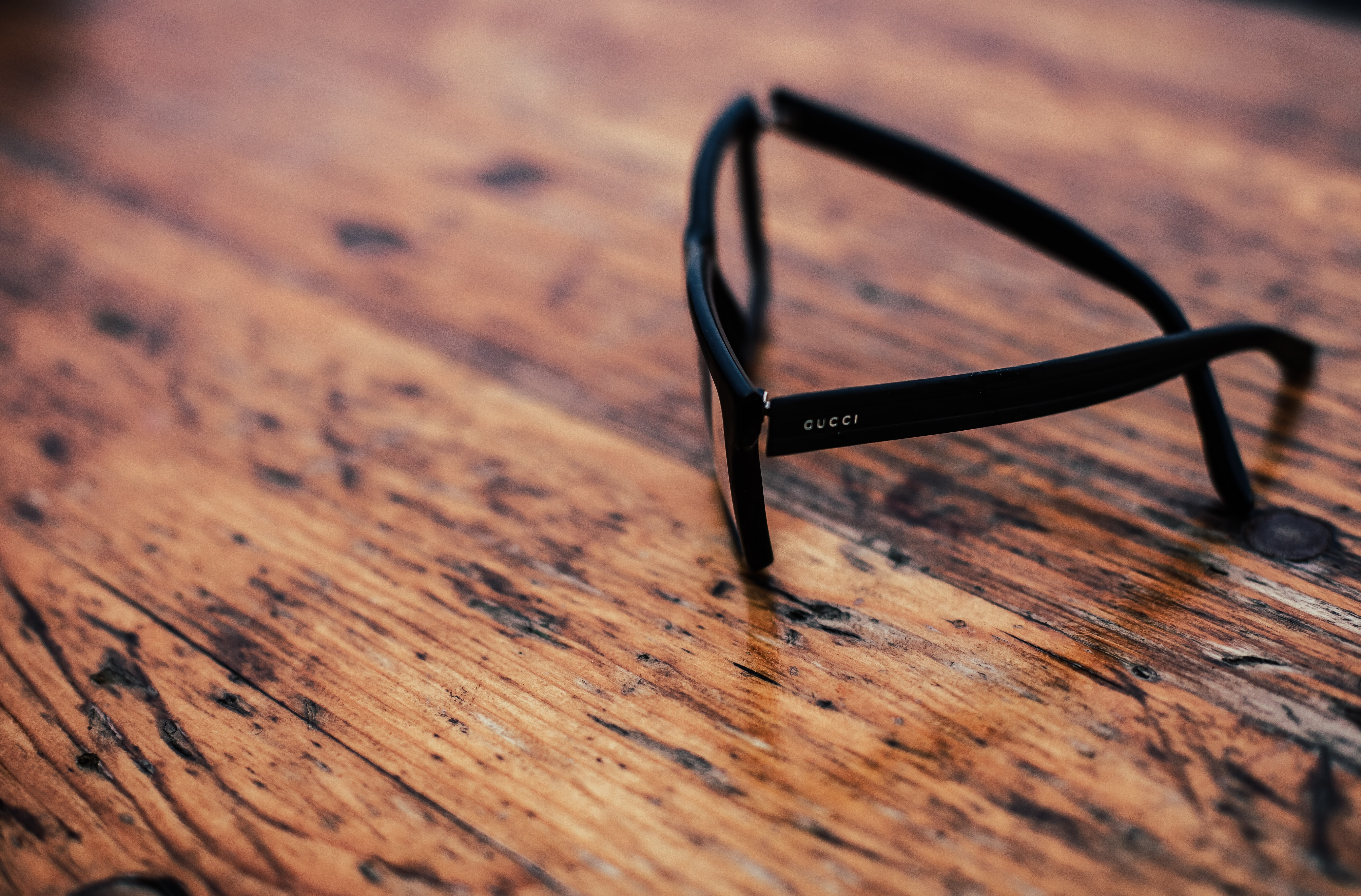 Gucci glasses with black frames on a wooden surface