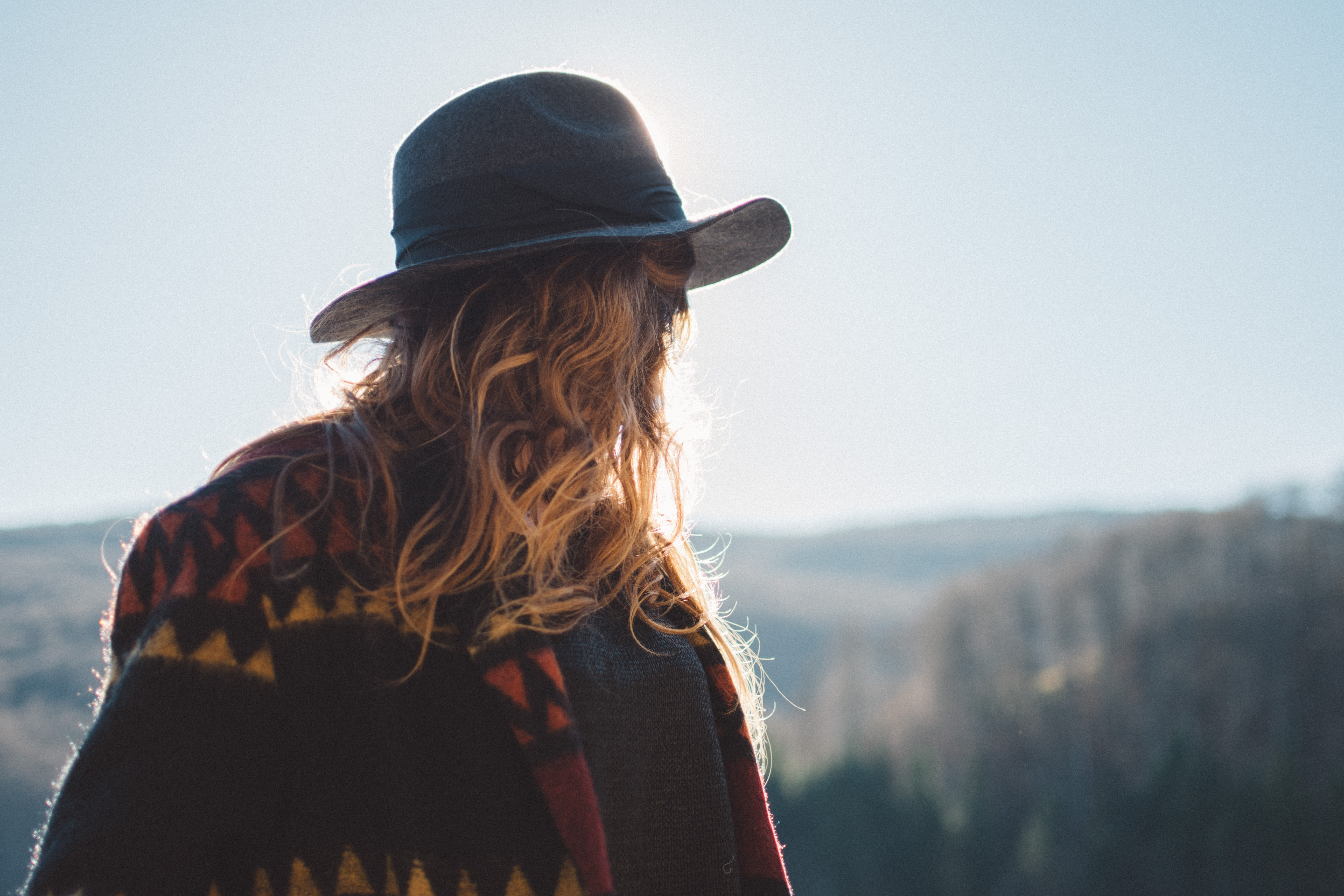A woman wearing Western-style clothing looking towards a hilly landscape.