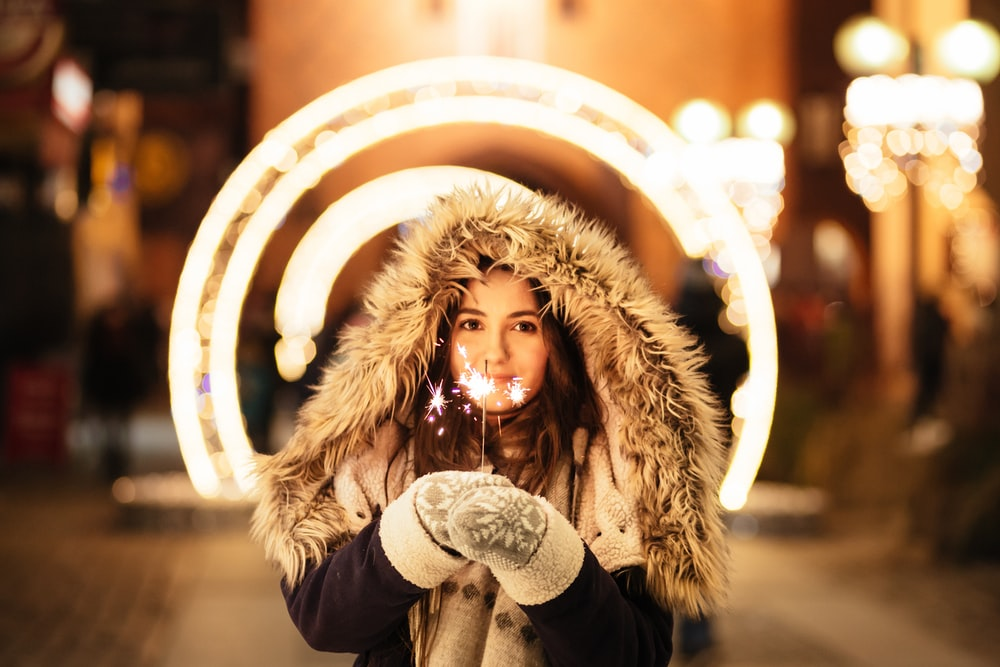 woman wearing coat and holding fireworks