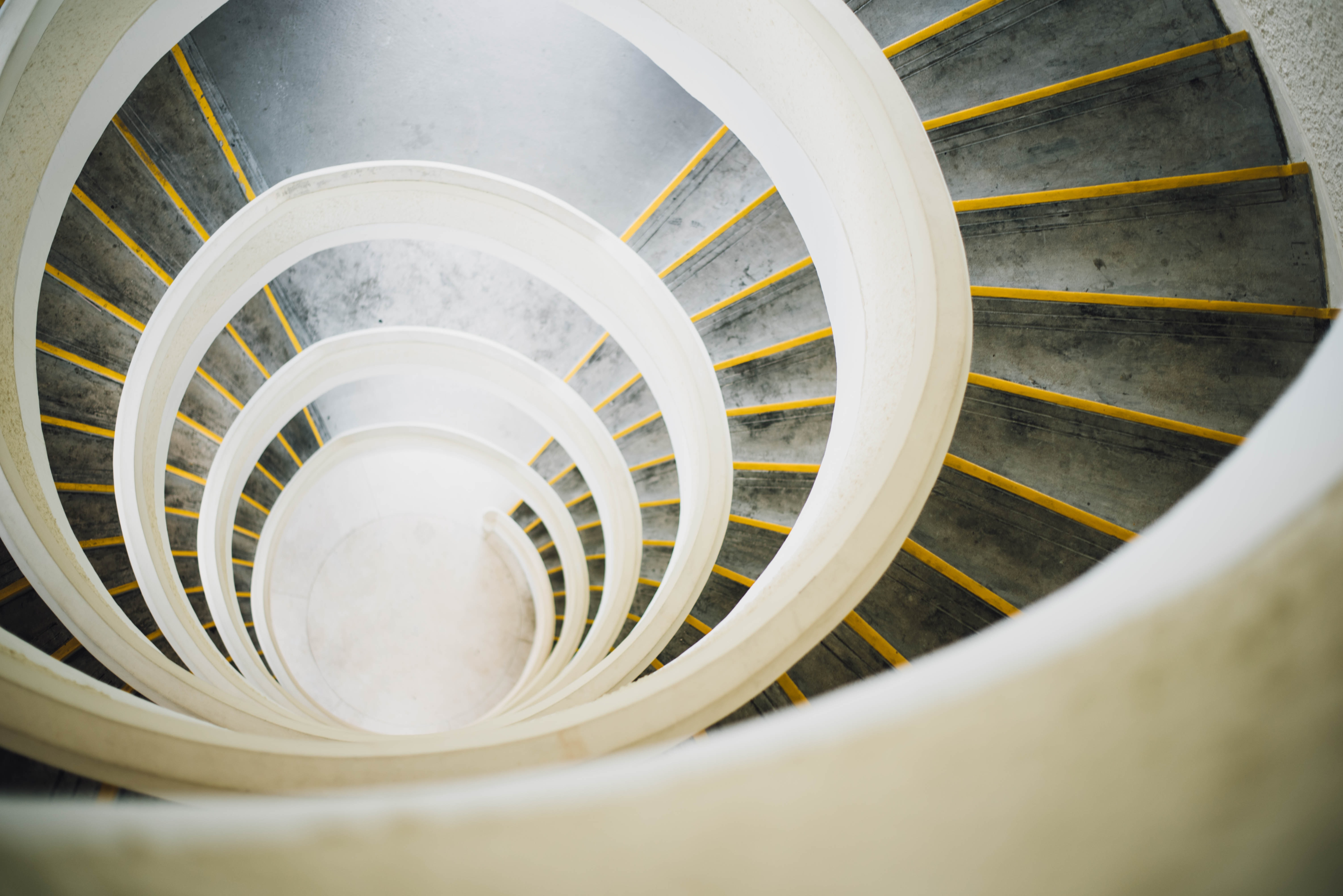 A white, grey, and yellow spiral staircase