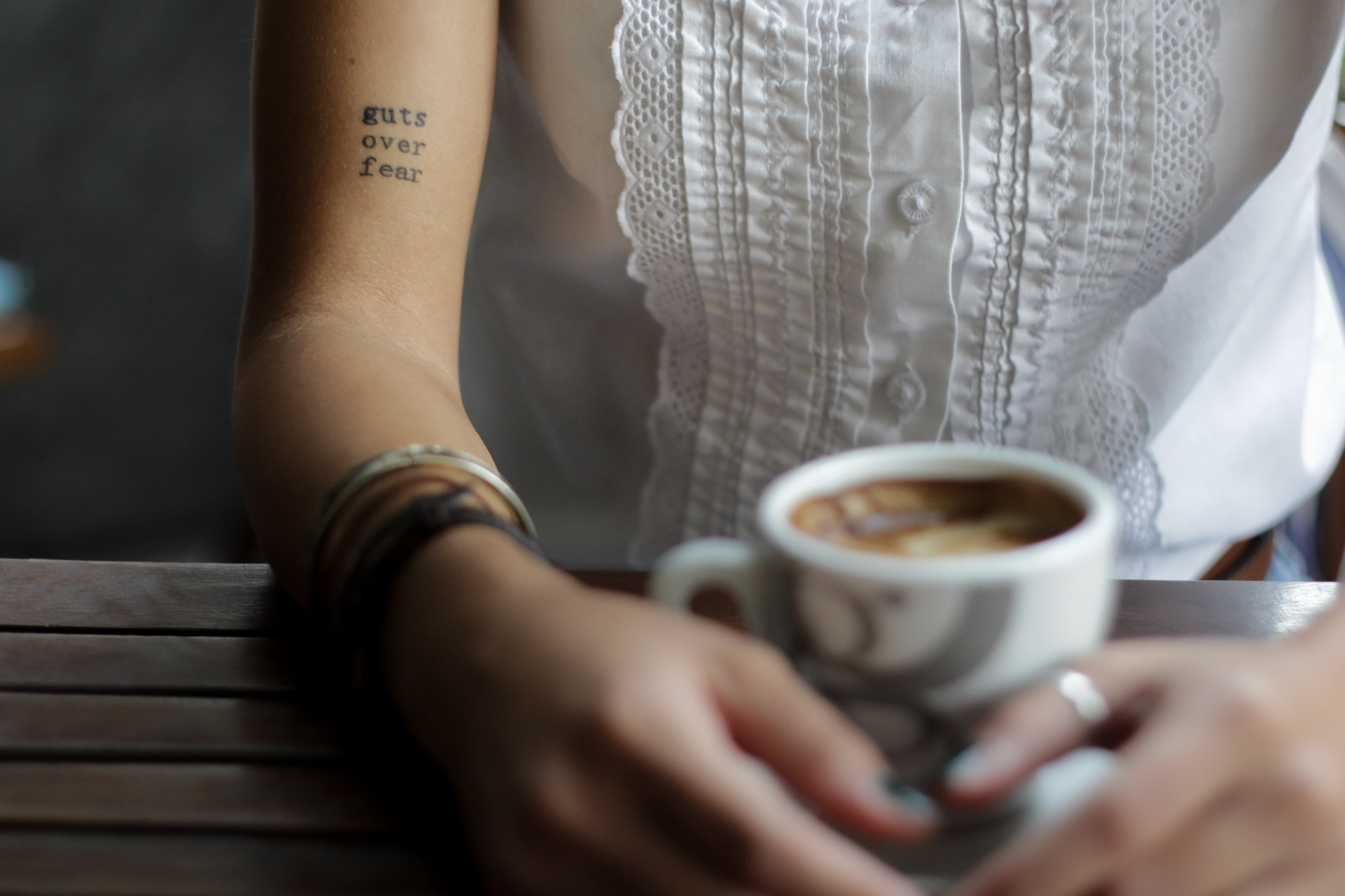 "A woman with a ""guts over fear"" tattoo sitting over coffee"