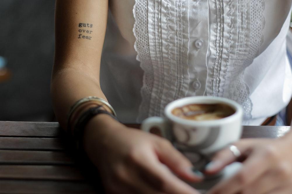 cô gái nắm tay trước ly cà phê