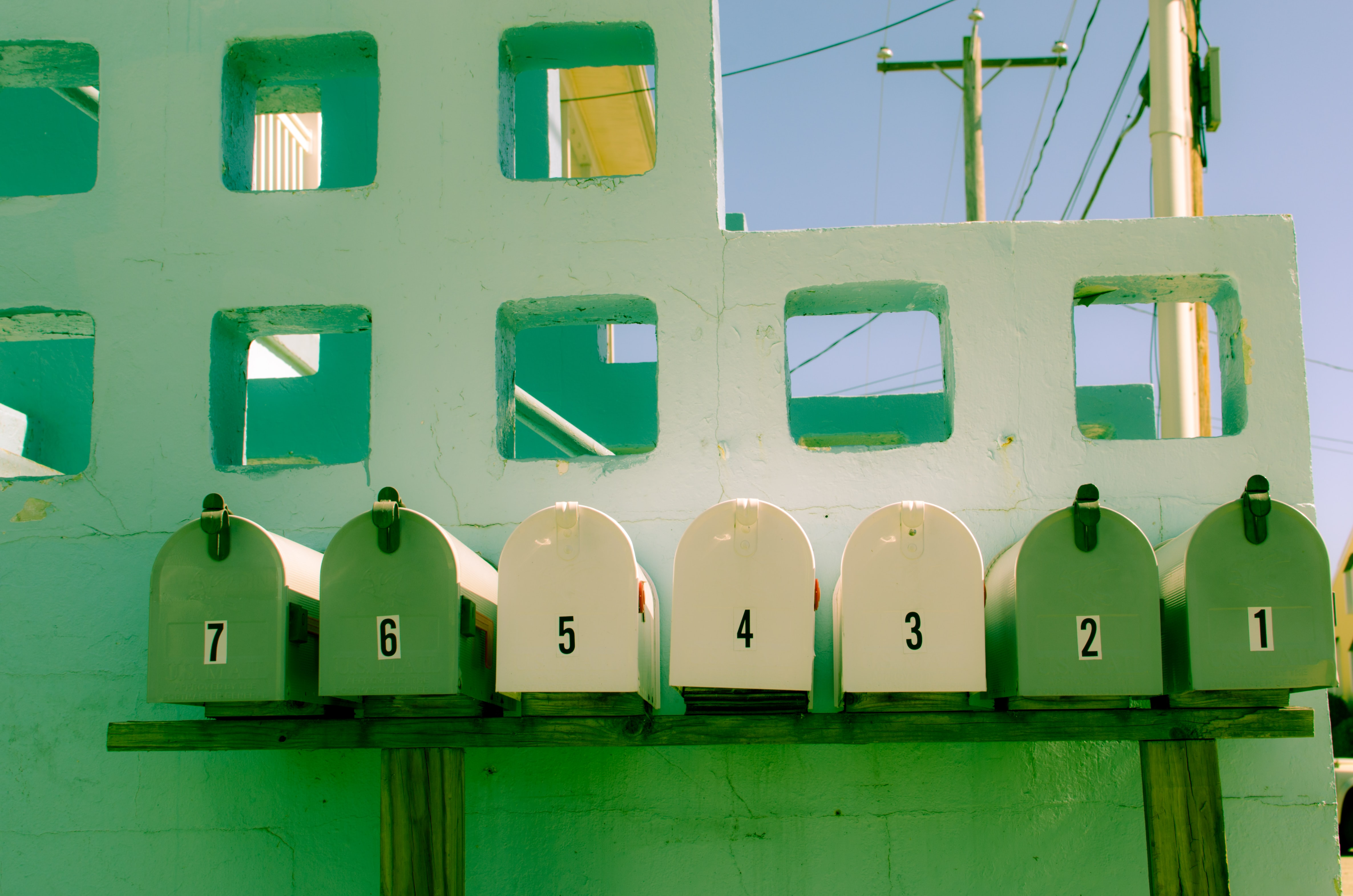 seven white and green mailboxes near white concrete wall