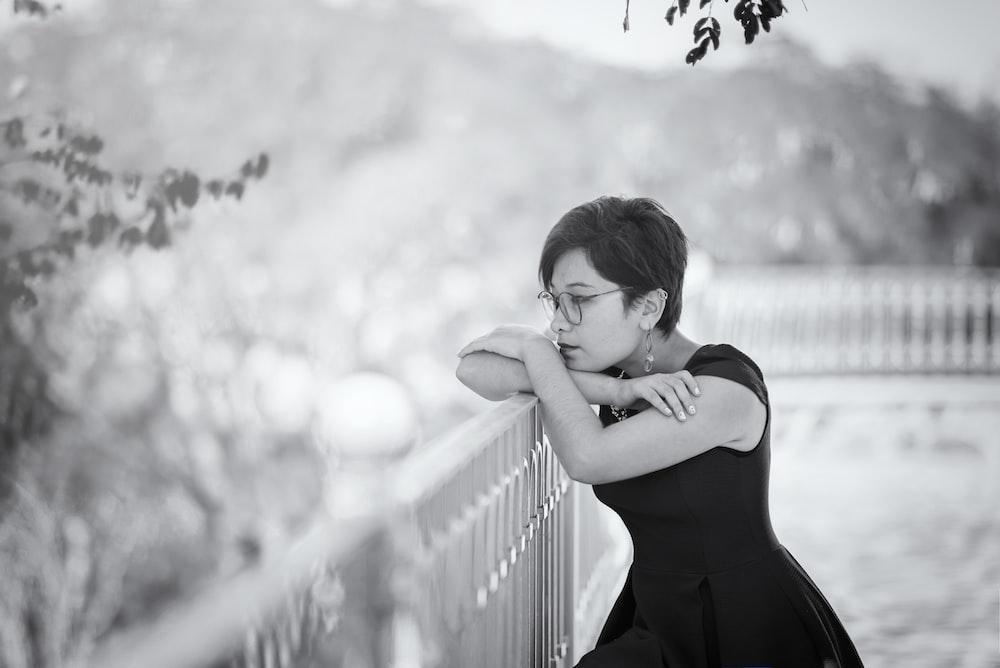 woman in black spaghetti strap dress standing beside railings