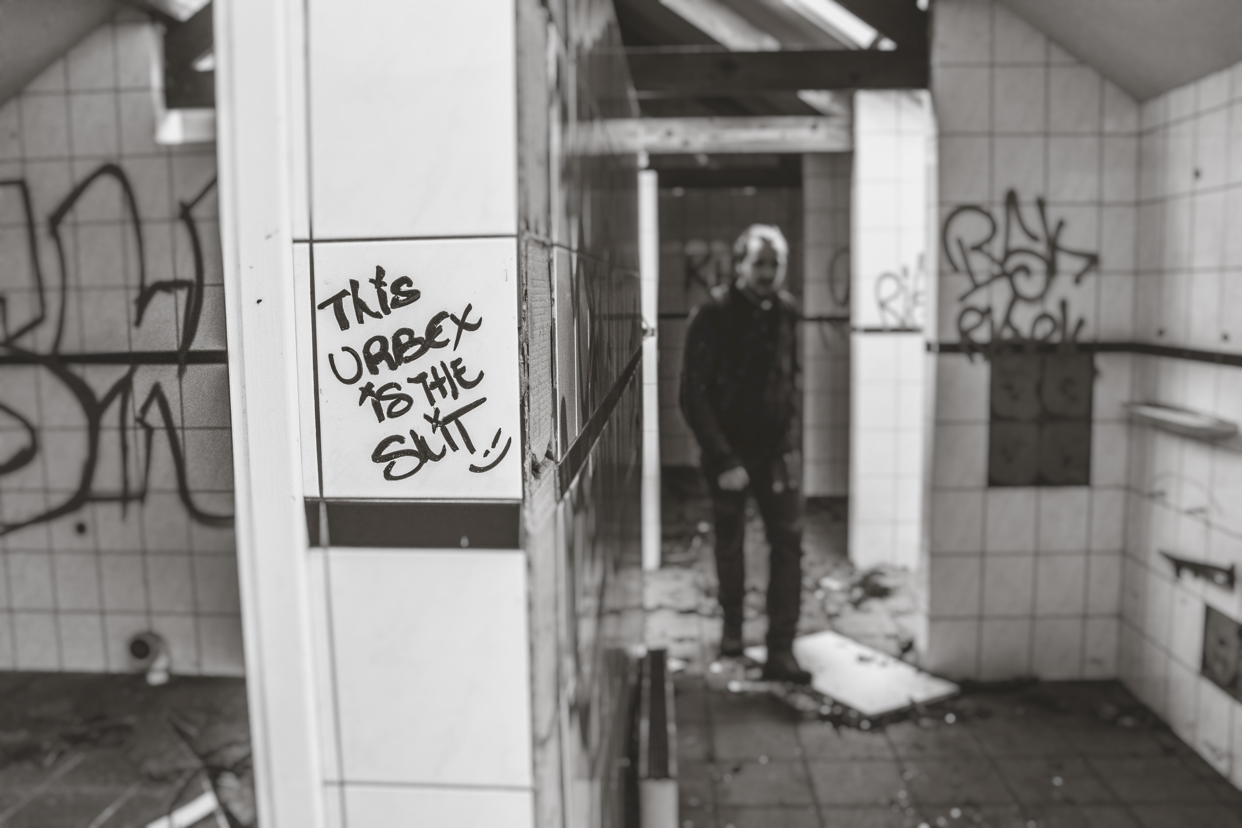 Black and white shot of person in decaying bathroom with graffiti on walls in Doel