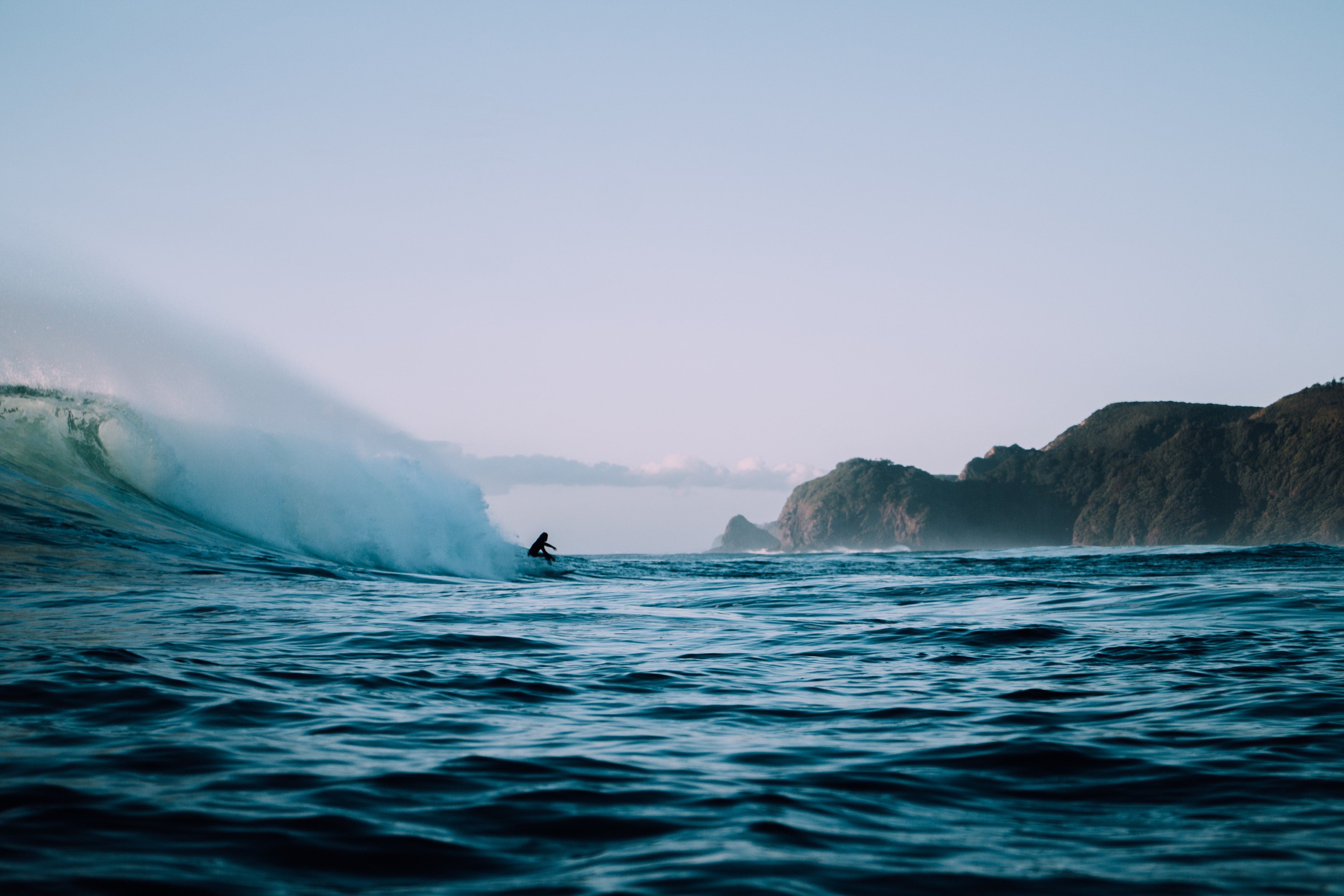 Surfer surfing on the ocean wave at Piha Beach