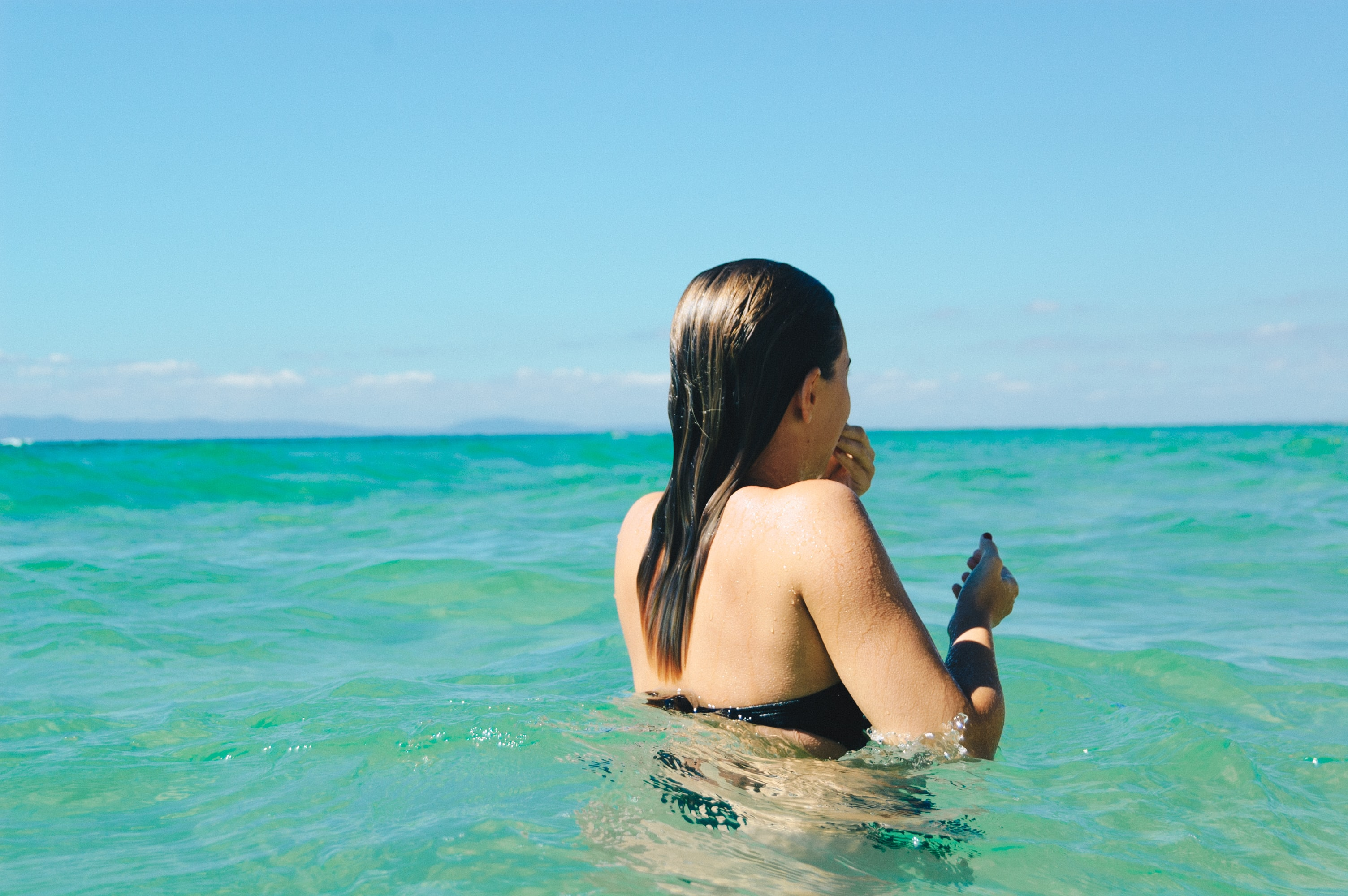 A woman swimming in the clear blue ocean with her hair wet in Melides