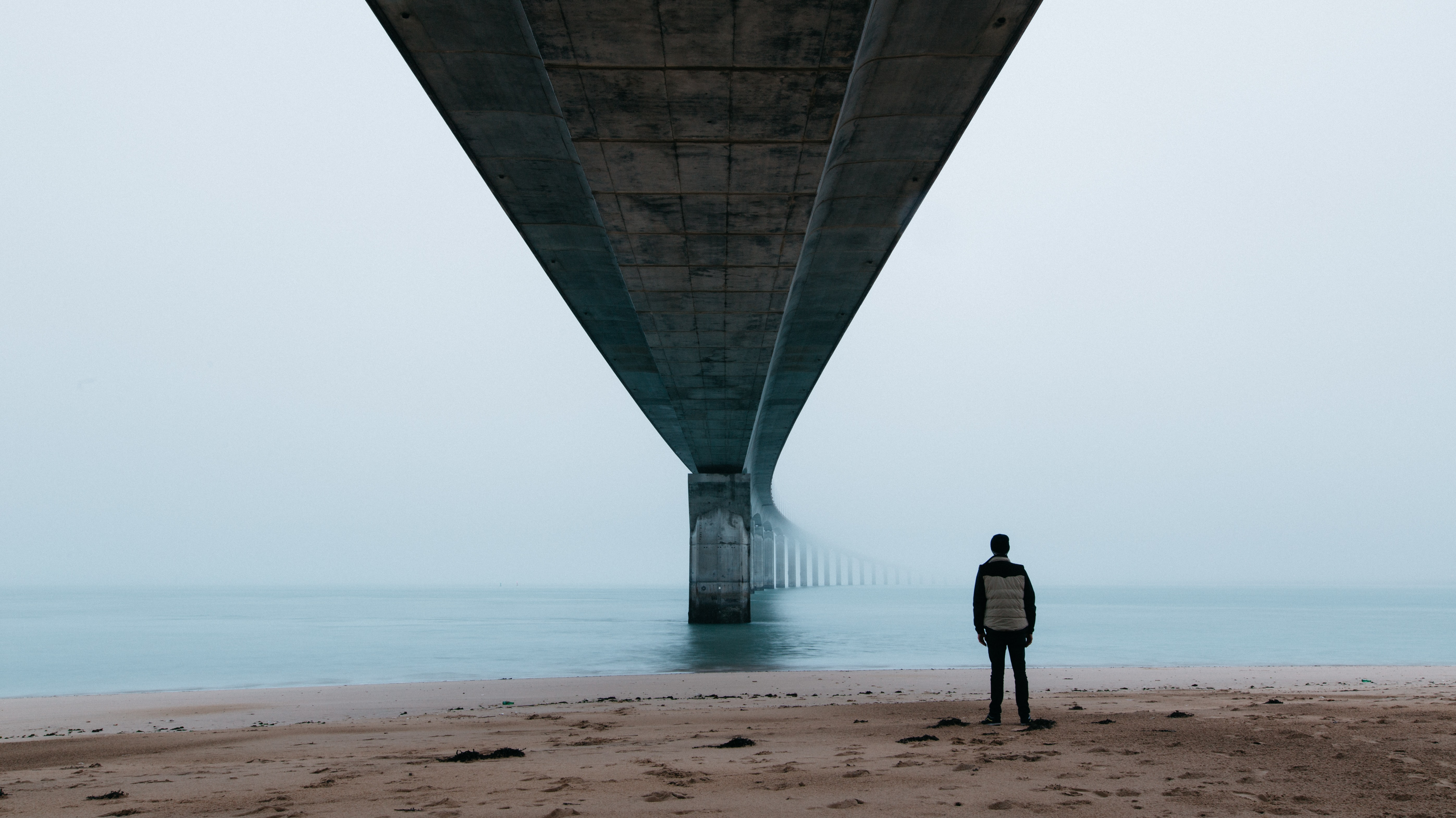 A man standing on the beach under a bridge looking out into an ocean covered in fog and mist
