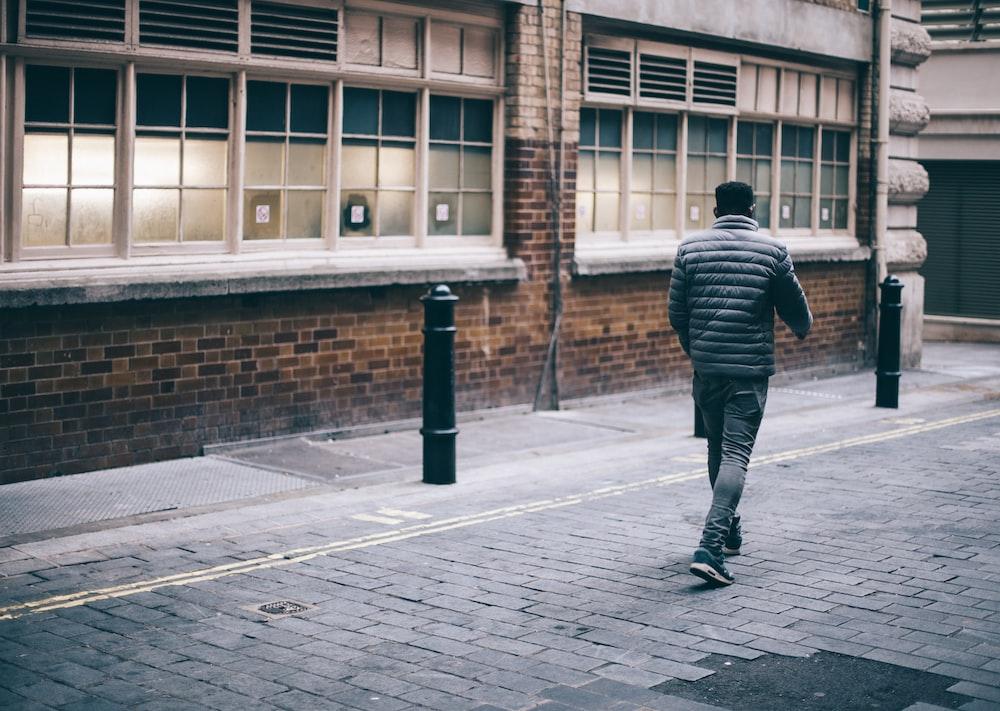 man walking beside brown concrete building during daytime