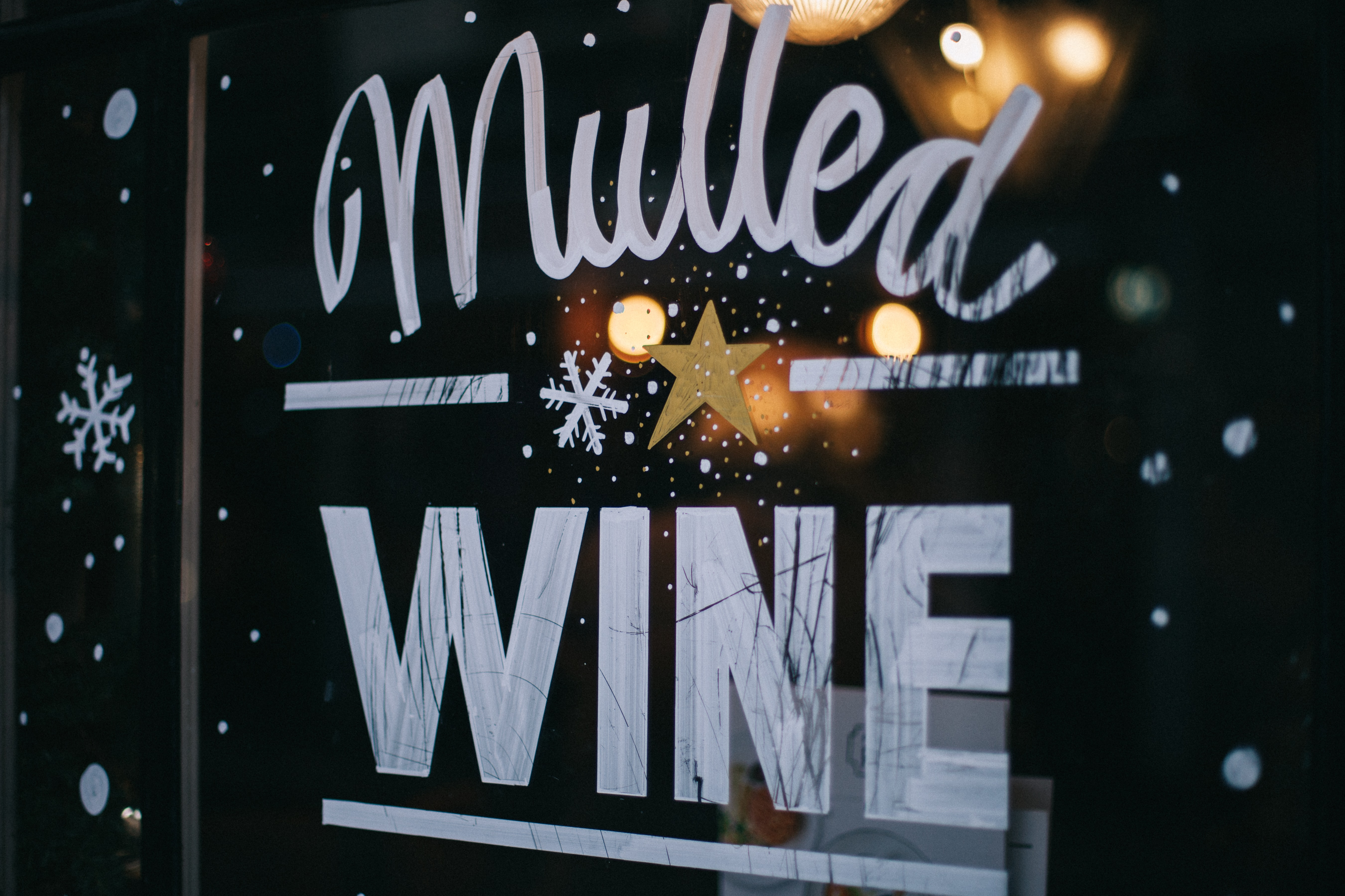 "An artwork reading ""mulled wine"" on a glass window of a store in Soho"