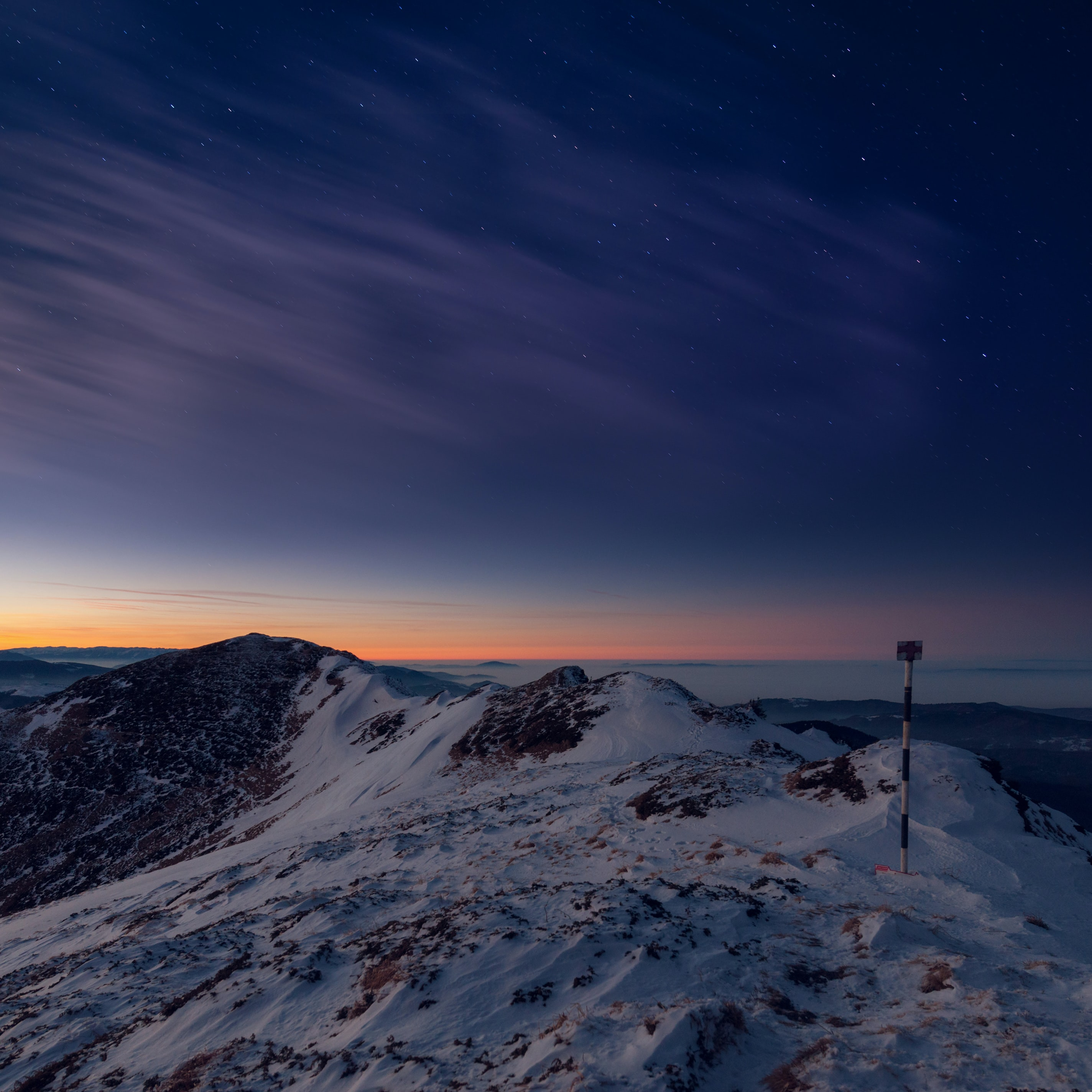 A distant sunset in the horizon as night falls over a snow covered Ciucas Peak