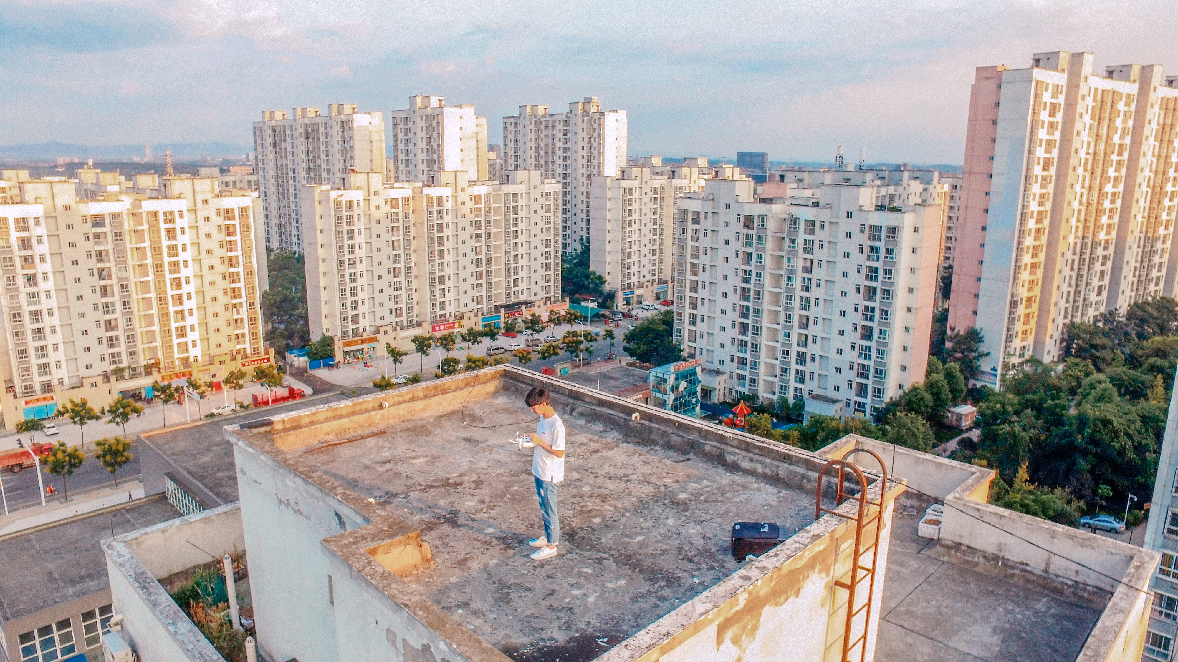 A young man stands on the rooftop which is surrounded by apartment buildings in Gongxingzhen.