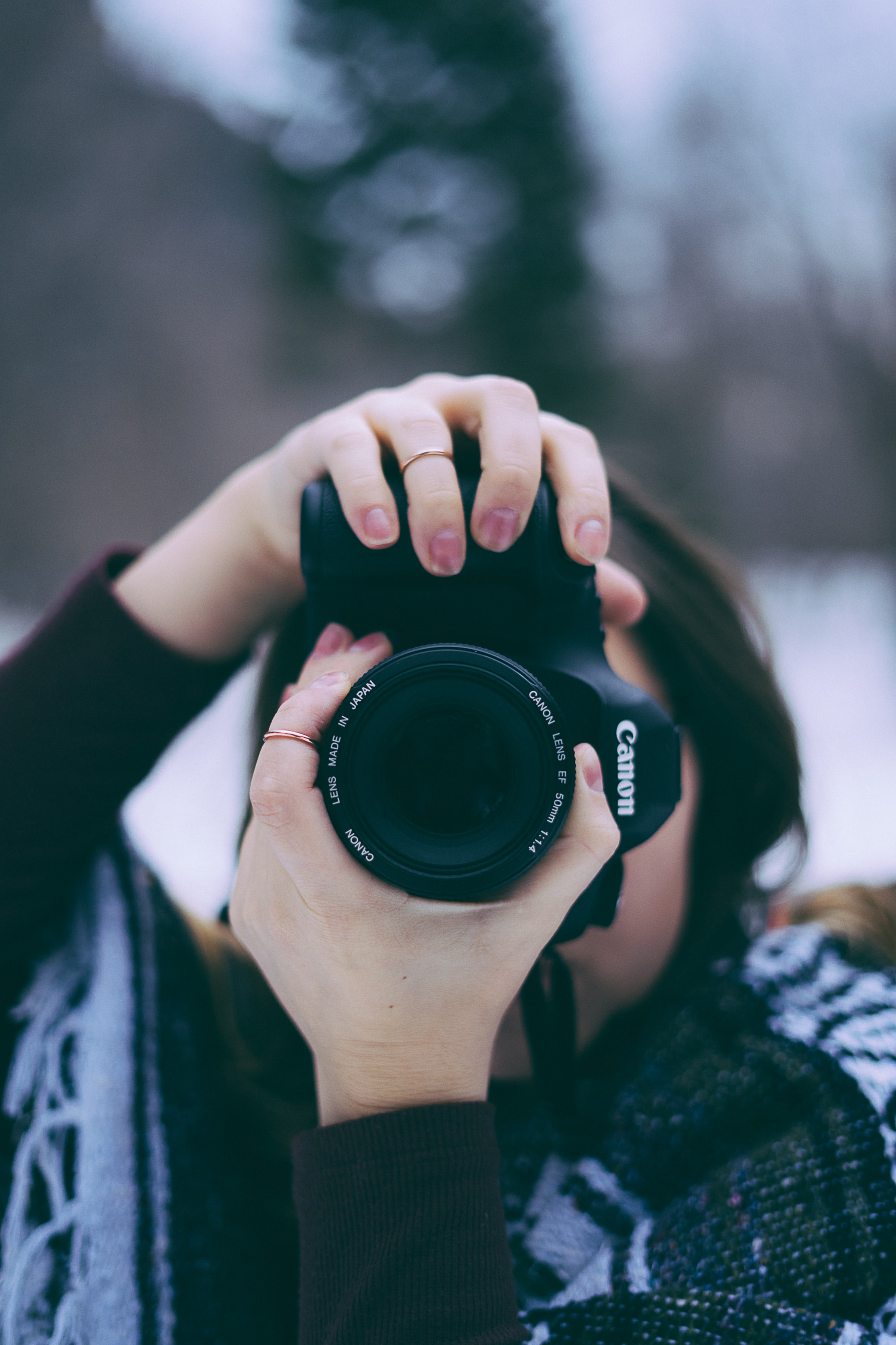 A woman taking a photo with a Canon camera in a wintry scenery