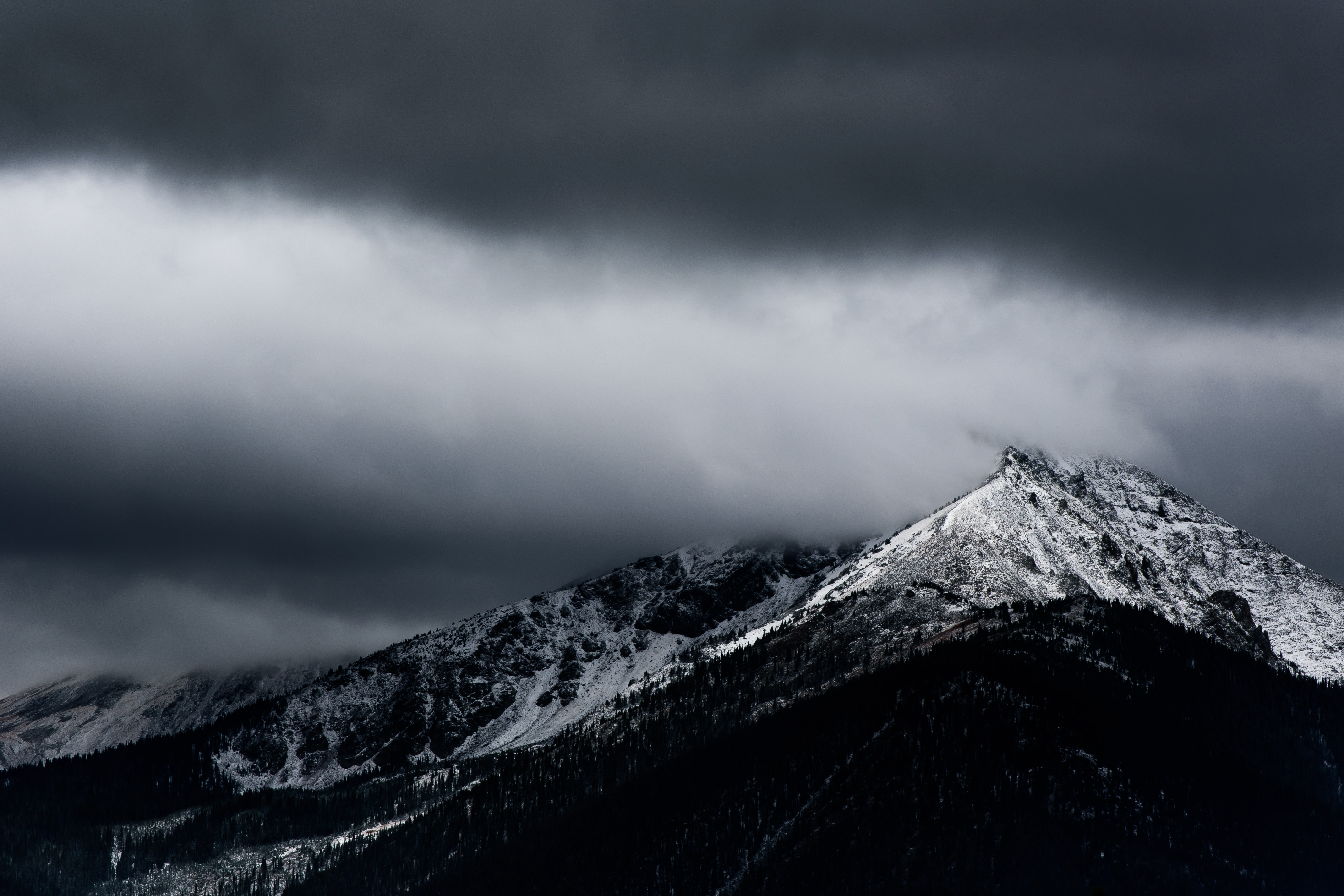Sharp snow-capped mountain ridge in Silverthorne under heavy gray clouds