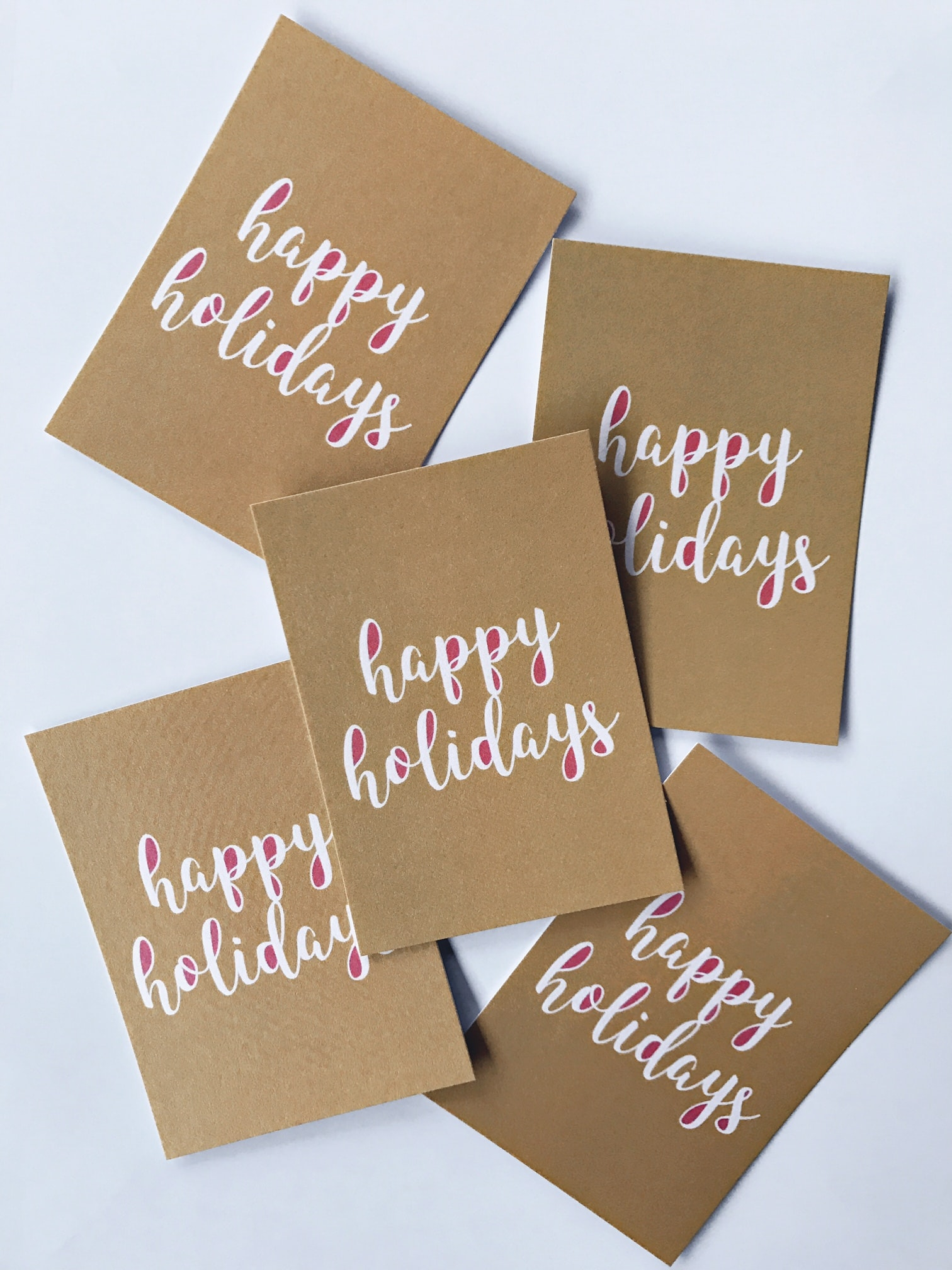 """Brown paper with white writing that says """"Happy Holidays."""""""