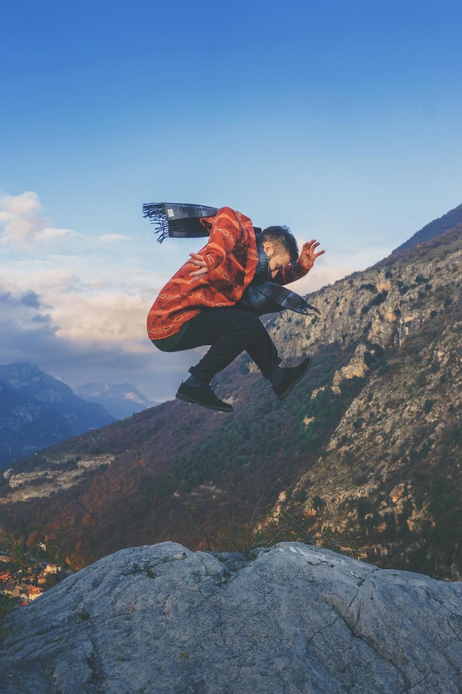 man doing stunt on cliff during daytime