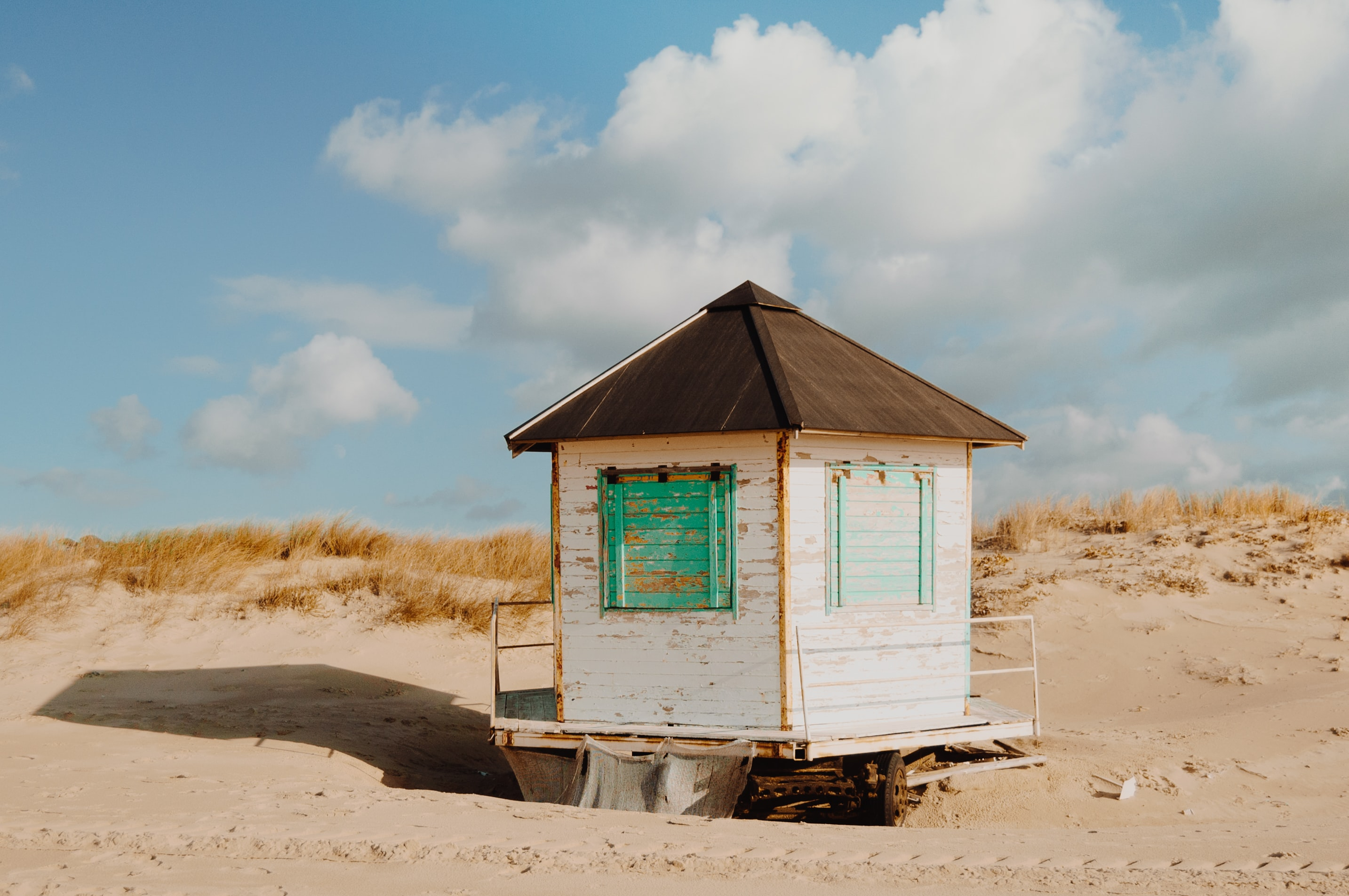 Old white wooden hut on a sand beach in Santo André