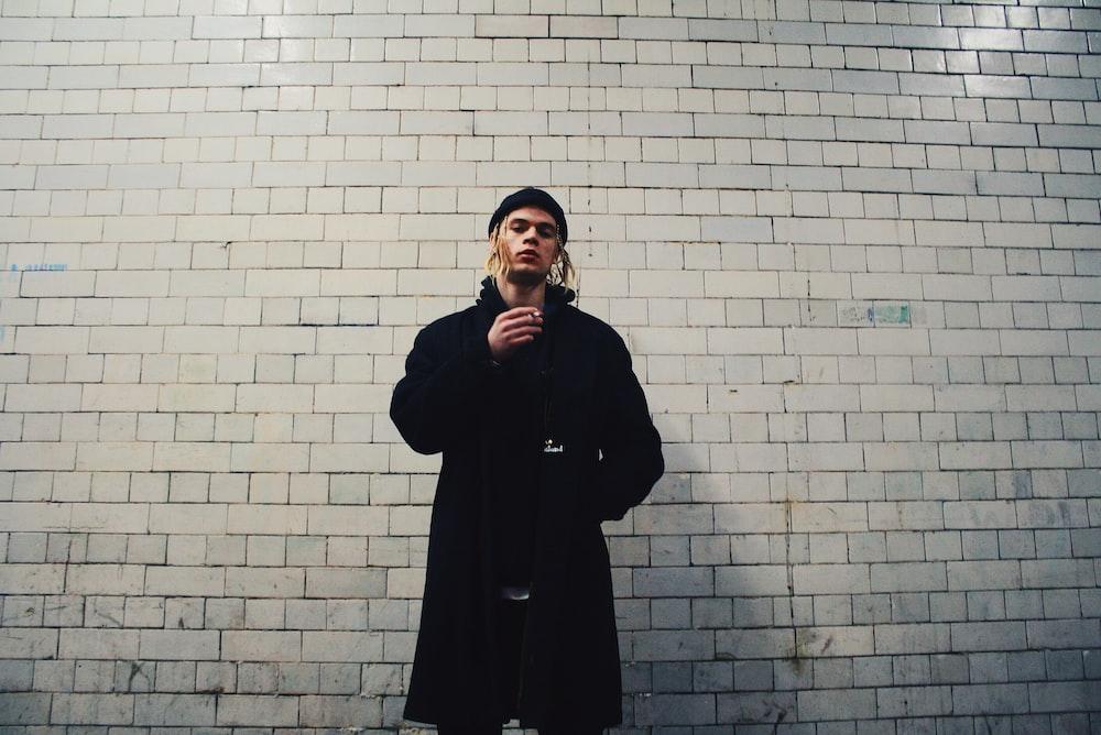 man standing near gray brick wall