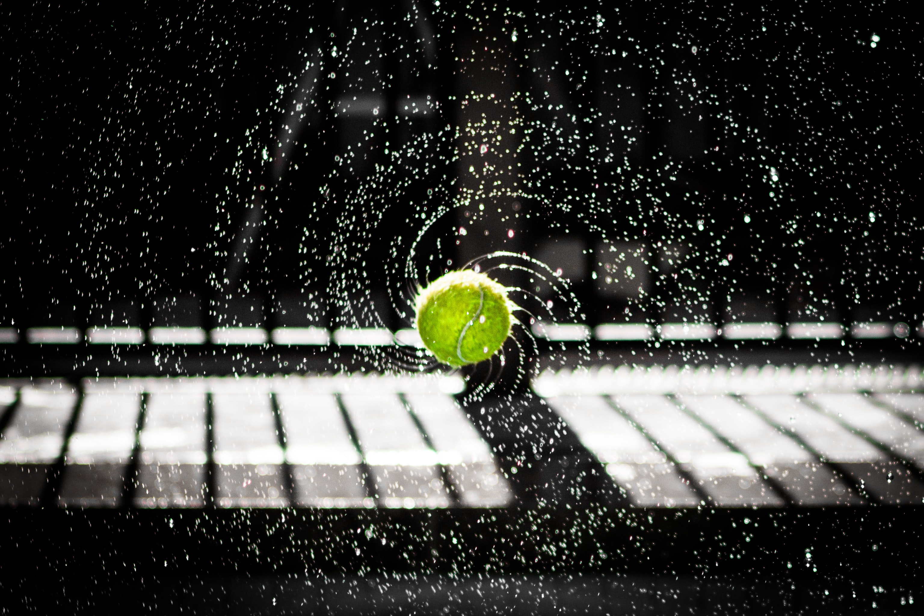Wet tennis ball spinning with the water spraying off