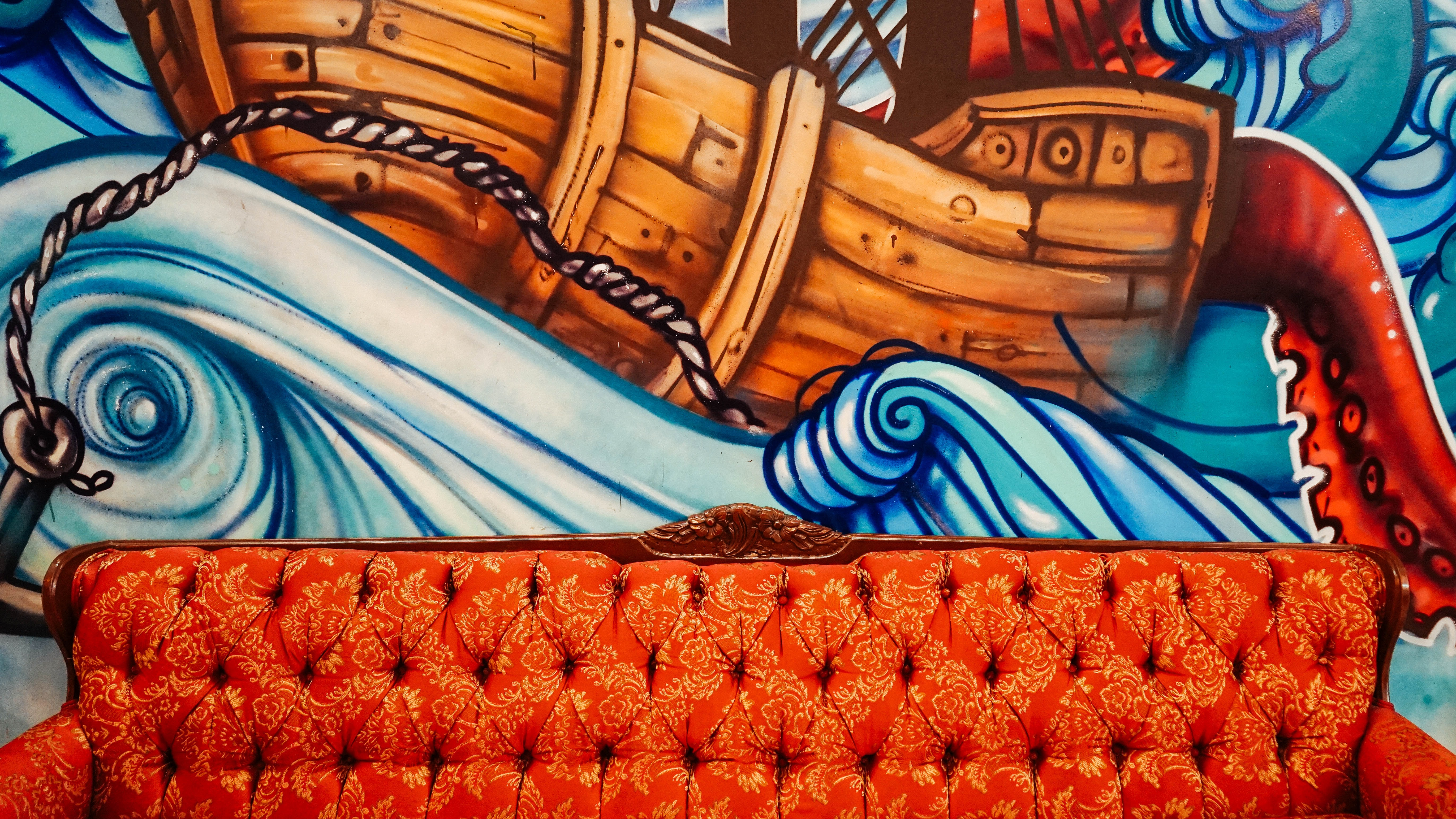 Long red sofa in front of graffiti mural of boat on rough seas at Cassava Roots