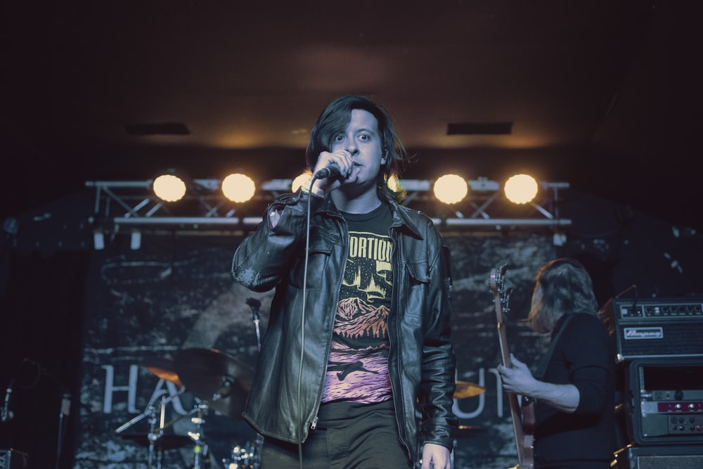 man in black leather jacket singing with microphone